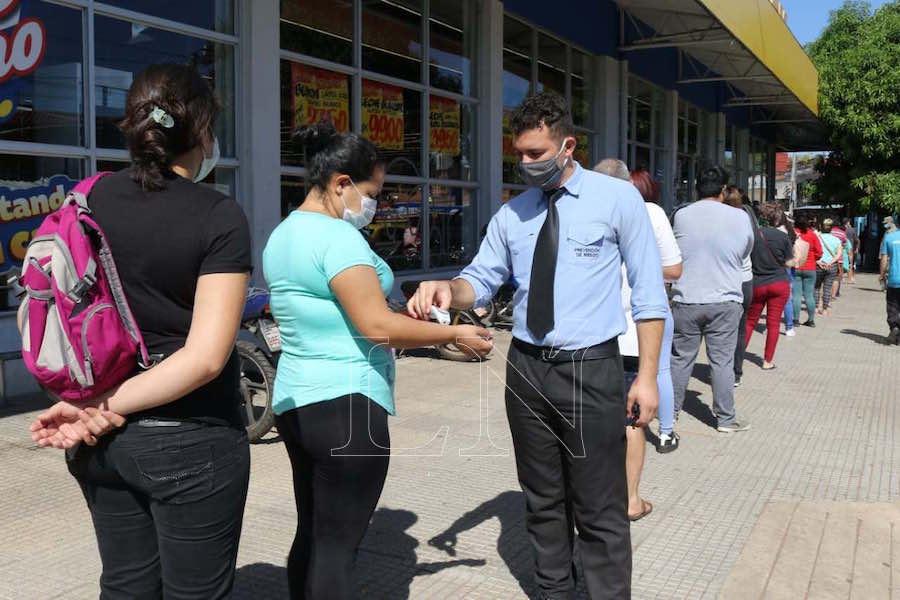 Un guardia de un supermercado toma la temperatura de un beneficiario del subsidio antes de ingresar y efectivizar la ayuda. Foto: Archivo.