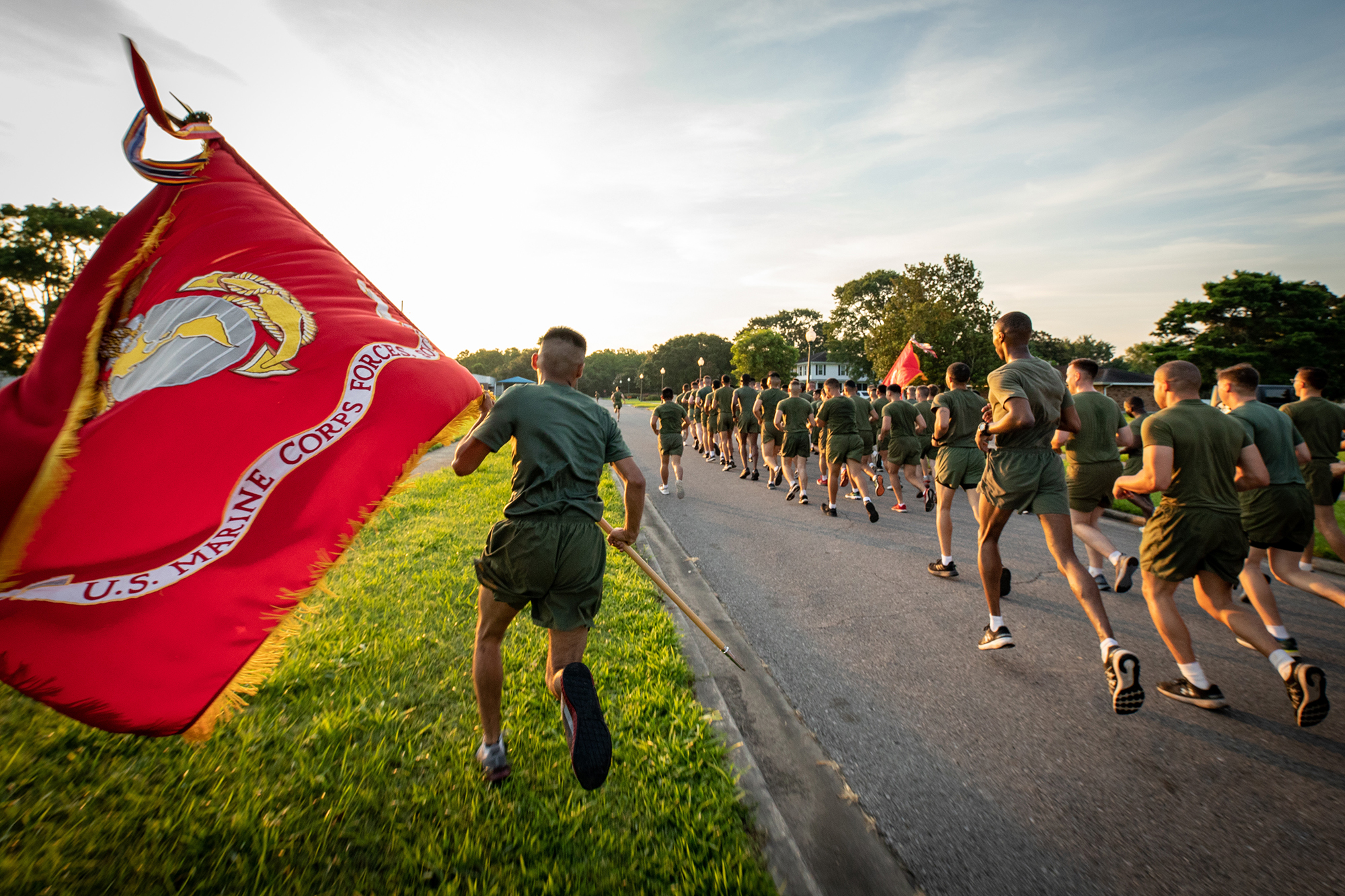 A U.S. Marine runs with the Marine Corps Forces South guidon during a formation run around Marine Corps Support Facility New Orleans on June 15, 2021. (Cpl. James Stanfield/Marine Corps)