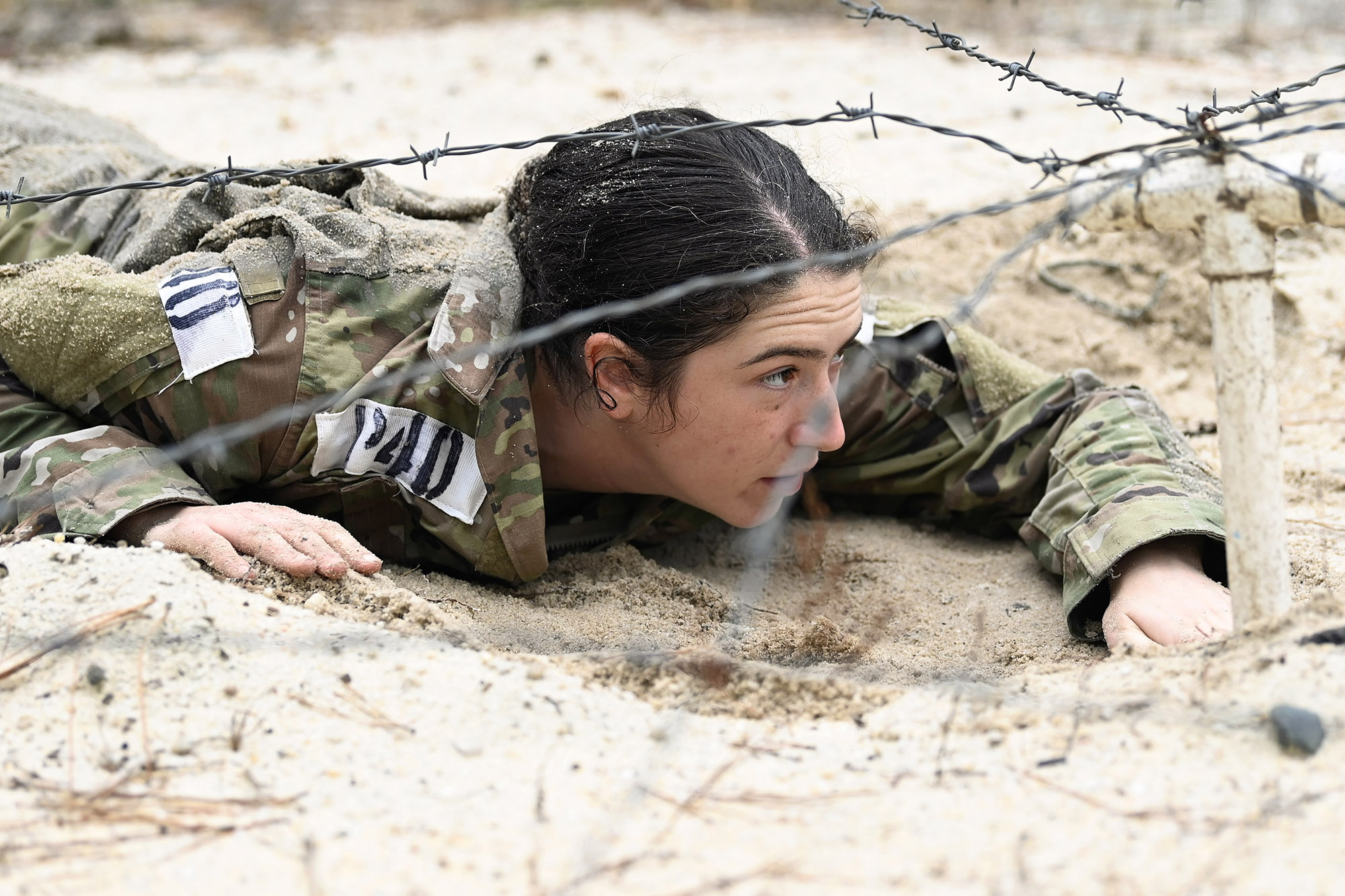 A soldier assigned to the U.S. Army John F. Kennedy Special Warfare Center and School low crawls under barbed wire during Psychological Operations Assessment and Selection at Camp Mackall, N.C., March 1, 2021. (K. Kassens/Army)