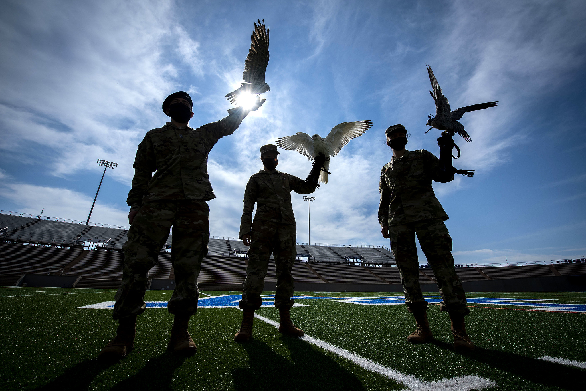 Cadet 2nd Class Kayla Steiner, center, handler of Nova, the newly named 15-week-old full white-phase Gyrfalcon, displays the new mascot of the U.S. Air Force Academy with Cadet 1st Class Seamus Kean, left, and Cadet 3rd Class Sierra Hillard, right. (Joshua Armstrong/Air Force)