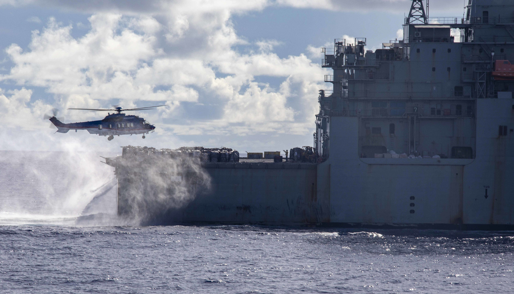 A U.S. Airbus H225 Super Puma helicopter conducts a replenishment-at-sea April 14, 2021, with the dry cargo and ammunition ship USNS Alan Shepard (T-AKE 3) and the amphibious assault ship USS Makin Island (LHD 8) in the Pacific Ocean. (Mass Communication Specialist Seaman Nadia Lund/Navy)