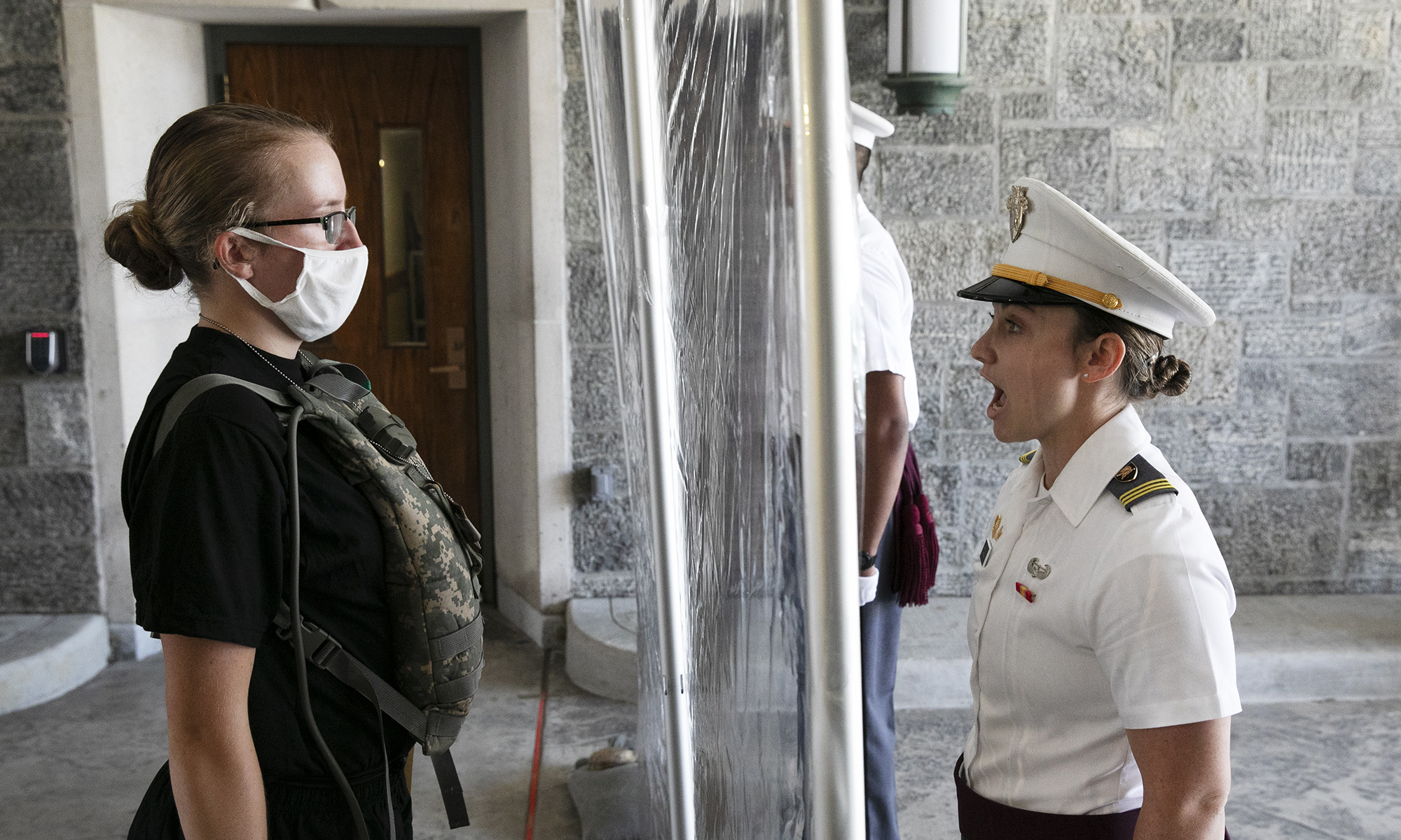 A new cadet, left, listens as First Class Cadet Madison Teague, right, yells commands as a plastic screen separates them at the U.S. Military Academy on July 13, 2020, in West Point, N.Y. The Army is welcoming more than 1,200 candidates from every state. Candidates will be COVID-19 tested immediately upon arrival, wear masks, and practice social distancing. (Mark Lennihan/AP)
