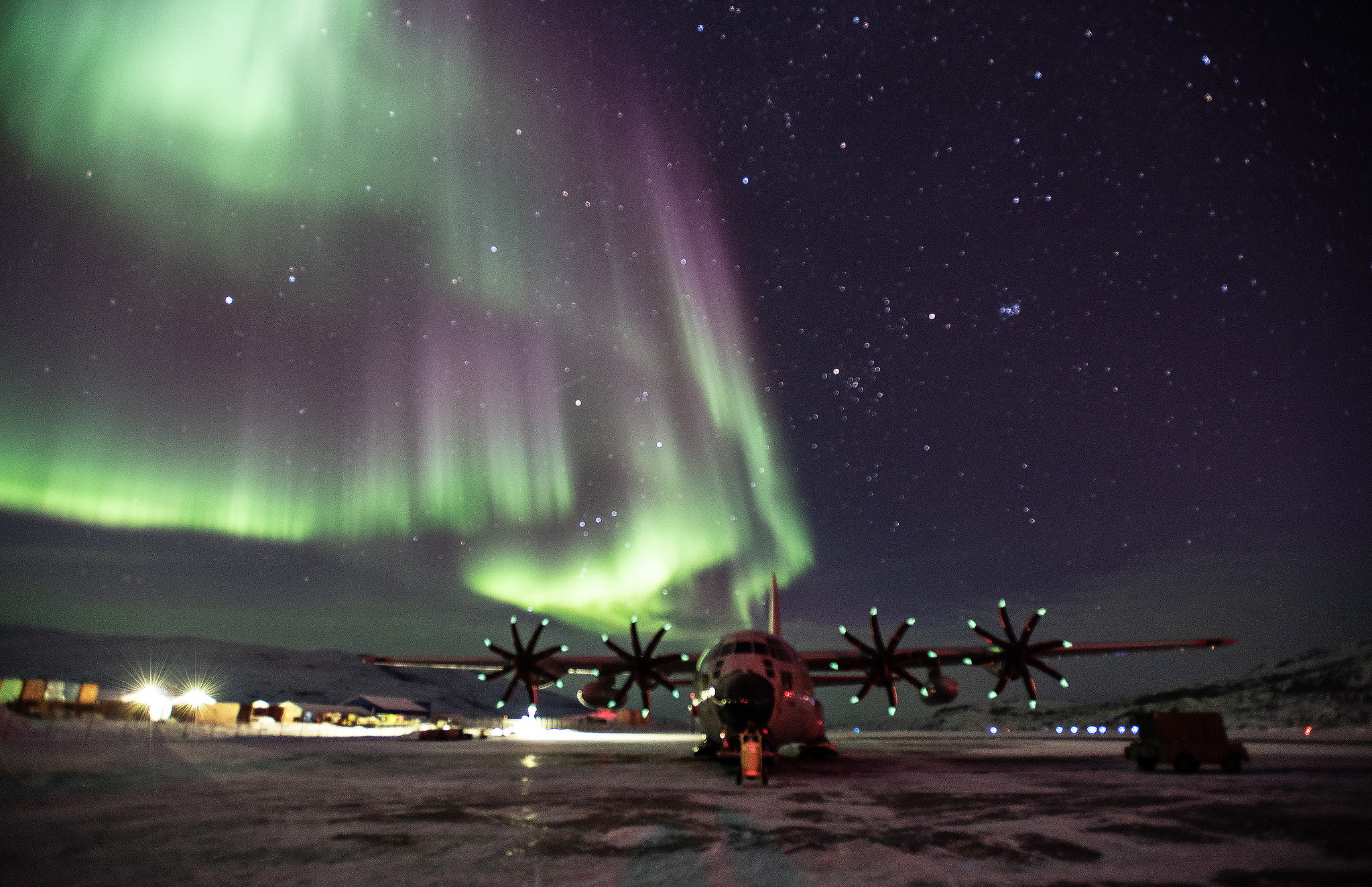 An LC-130 Skibird from the 109th Airlift Wing sits on the ramp at Kangerlussuaq Airport, Greenland, with the Northern Lights dazzling in the sky above. (Lt. Col. Kevin Jones/National Guard)