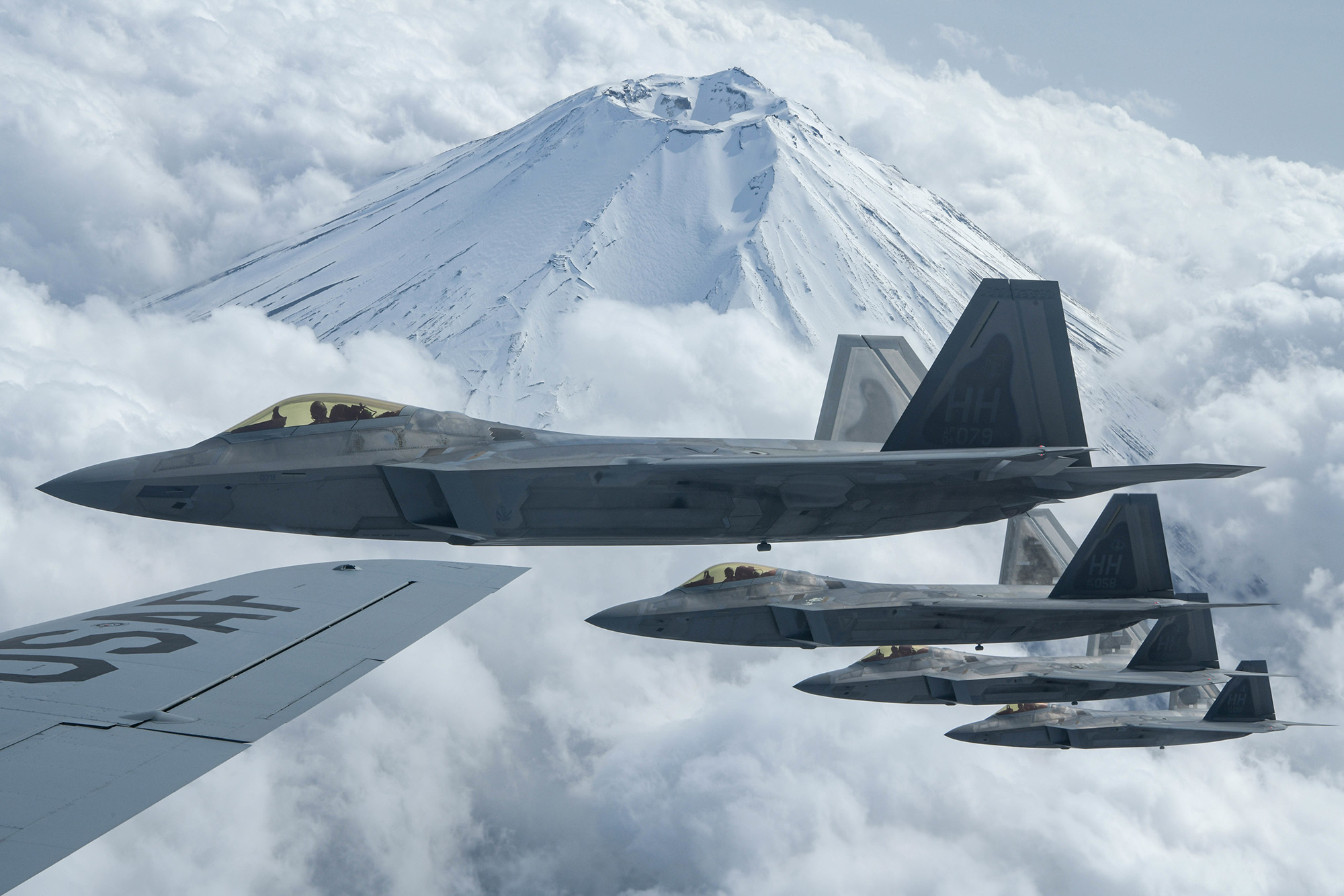 Four F-22 Raptors fly alongside a U.S. Air Force KC-135 Stratotanker during fifth-generation fighter training near Mount Fuji, Japan, April 1, 2021. (Senior Airman Rebeckah Medeiros/Air Force)