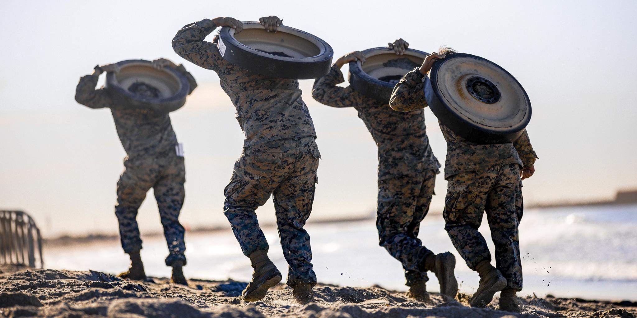 Marines with 1st Marine Division carry track wheels during the Amphibious Combat Endurance Test on Marine Corps Base Camp Pendleton, Calif., Jan. 15, 2021. (Lance Cpl. Roxanna Ortiz/Marine Corps)