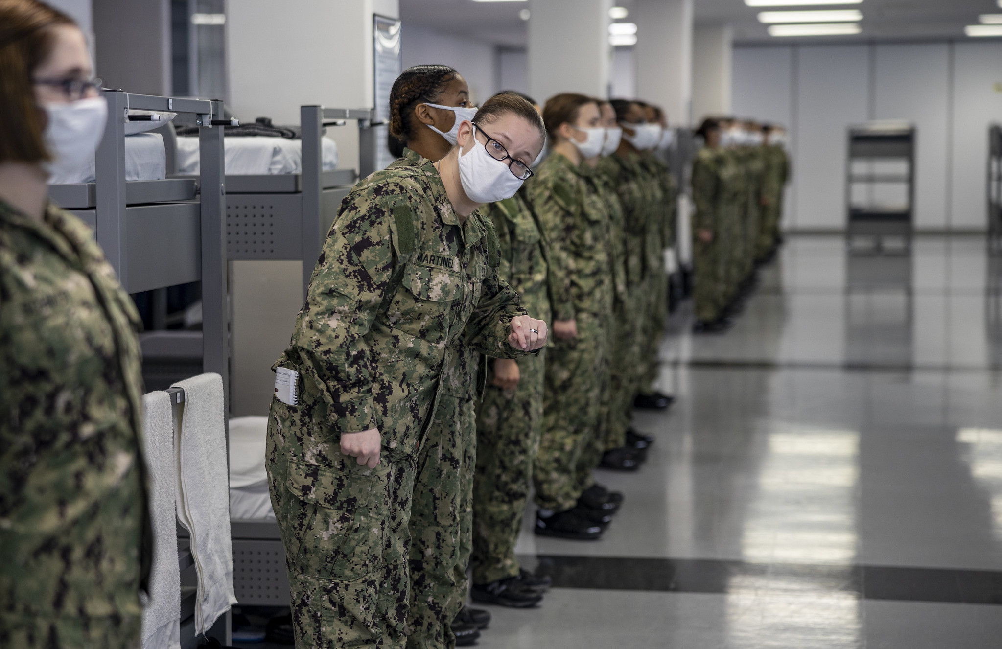 Seaman recruit Shanda Martinez, a recruit chief petty officer, checks to see if her division is ready for their first task during a dynamic material inspection Dec. 21, 2020, at Recruit Training Command at Great Lakes, Ill. (MC1 Camilo Fernan/Navy)