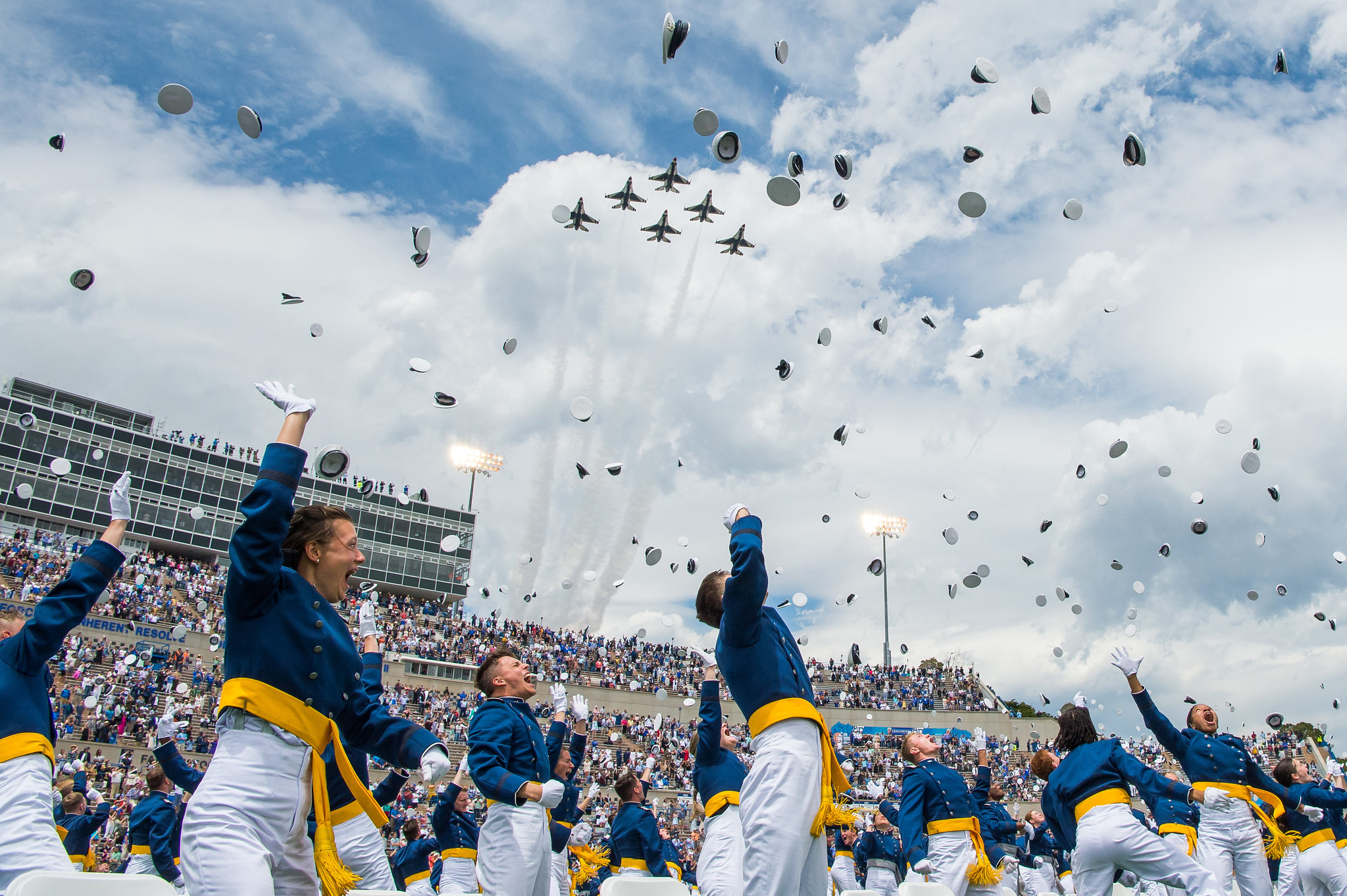 The U.S. Air Force Academy Class of 2021 graduates toss their hats skyward as the U.S. Air Force Thunderbirds roar overhead during the graduation ceremony in Colorado Springs, Colo., May 26, 2021. One-thousand-nineteen cadets crossed the stage to become the Air Force/Space Force's newest second lieutenants. (Trevor Cokley/Air Force)