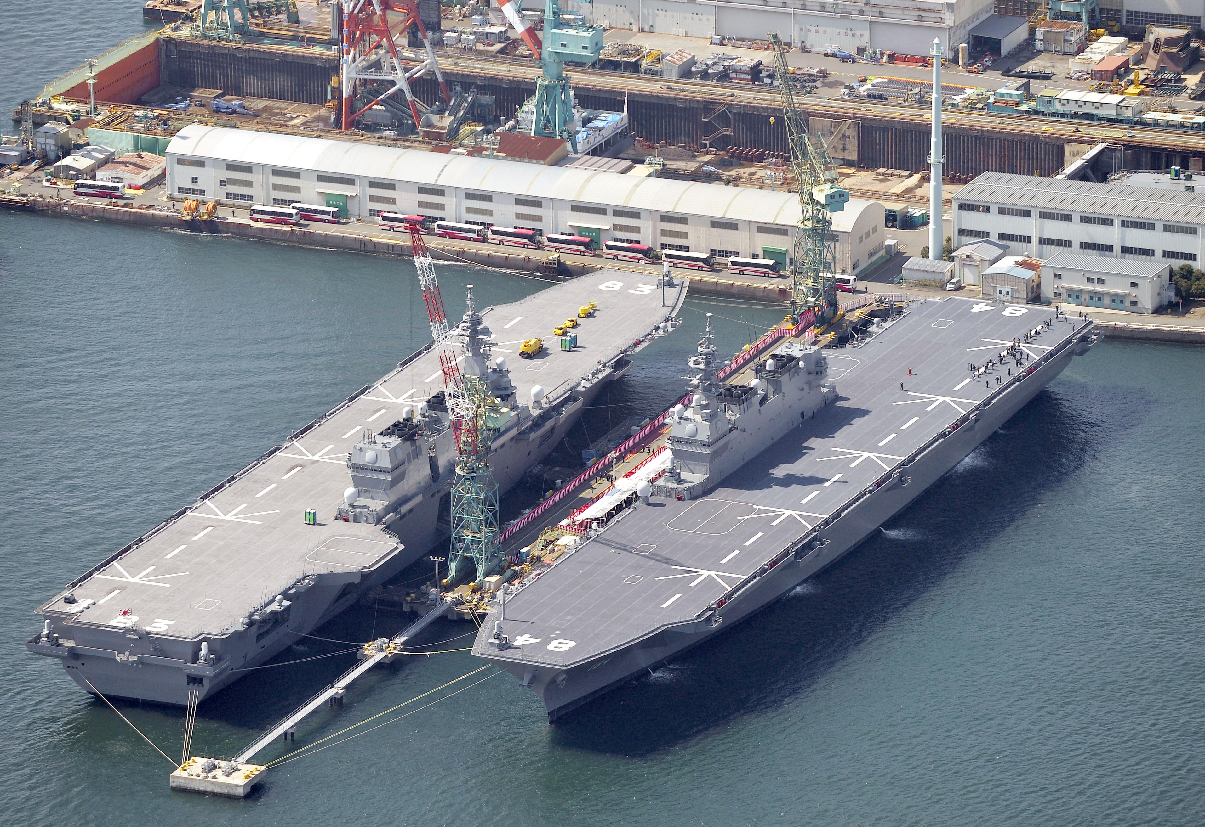 The Japan Maritime Self-Defense Force's helicopter carrier Kaga, right, and the Izumo are seen in Yokohama, south of Tokyo. (Yoshitaka Sugawara/Kyodo News via AP)
