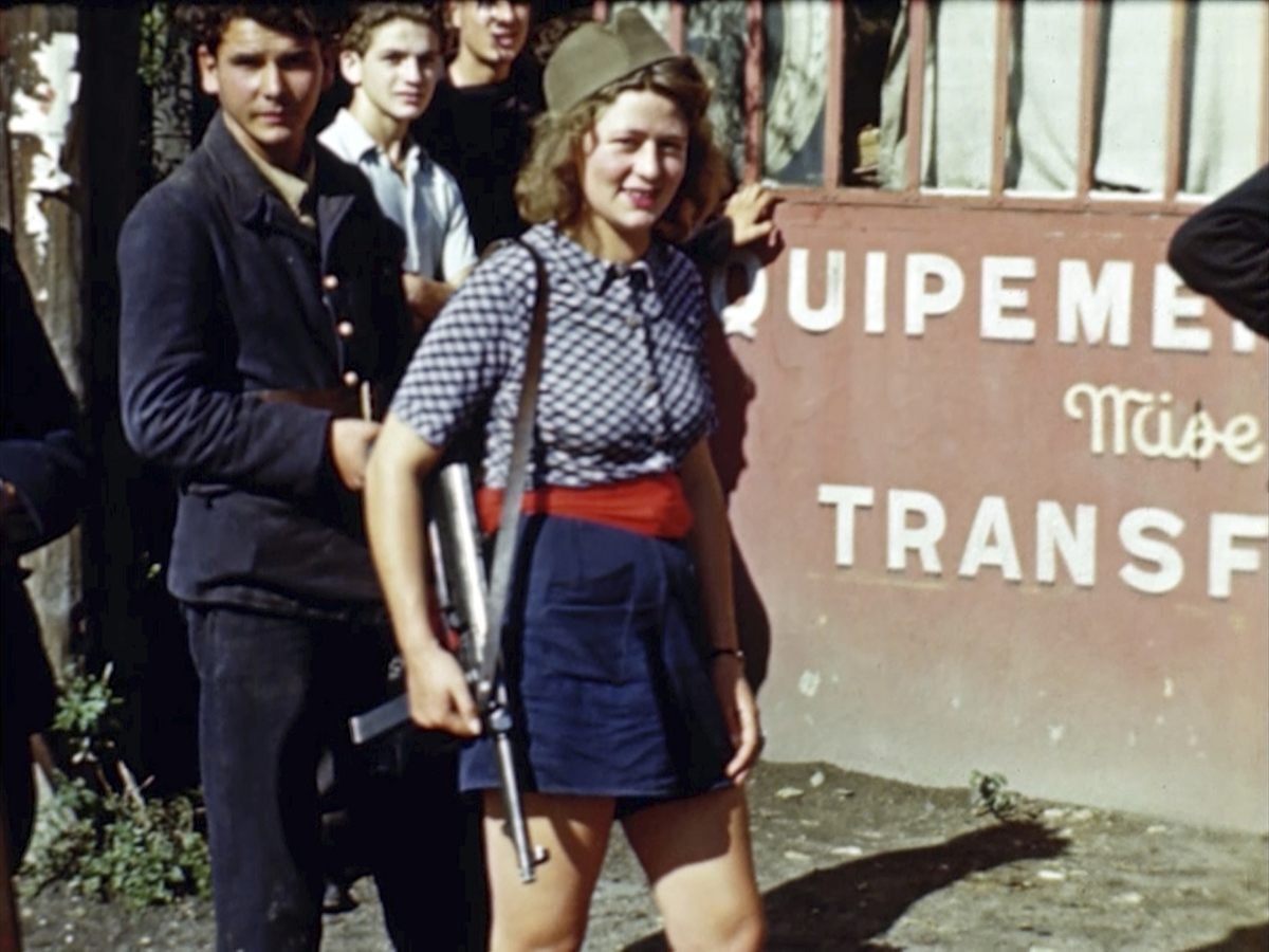 A French girl holding a weapon watches U.S. troops drive past after the liberation of Paris in August 1944. Seventy-five years later, surprising color images of the D-Day invasion and aftermath bring an immediacy to wartime memories. They were filmed by Hollywood director George Stevens and rediscovered years after his death. (War Footage From the George Stevens Collection at the Library of Congress via AP)