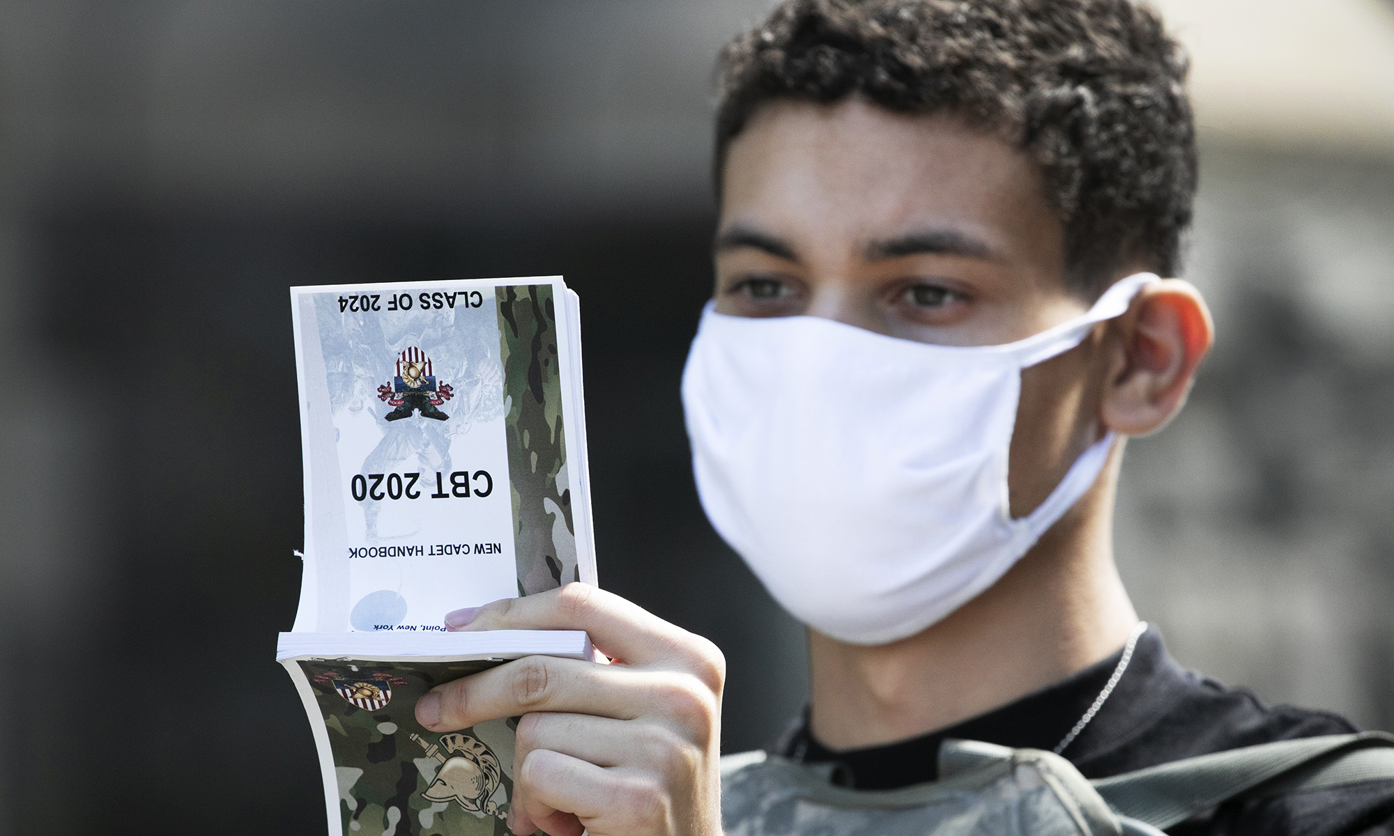 A West Point cadet reads the New Cadet Handbook on his first day at the U.S. Military Academy on July 13, 2020, in West Point, N.Y. The Army is welcoming more than 1,200 candidates from every state. Candidates will be COVID-19 tested immediately upon arrival, wear masks, and practice social distancing. (Mark Lennihan/AP)