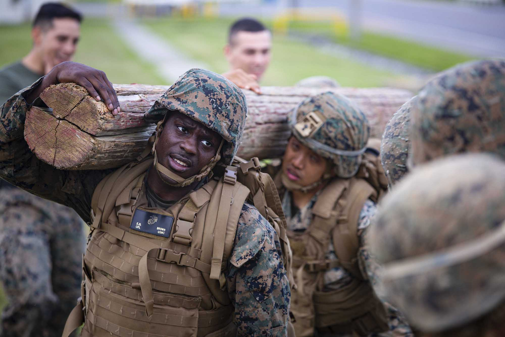 Cpl. Elbert Brown carries a log during the culminating event of the Marine Corps Martial Arts Program Instructor Course April 9, 202, on Marine Corps Air Station Futenma, Okinawa, Japan.(Staff Sgt. Lucas Vega/Marine Corps)