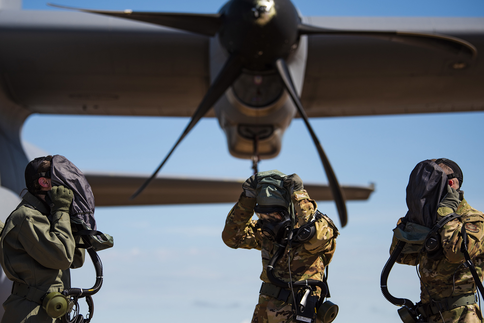 First Lt. Coltan Nading, 40th Airlift Squadron pilot, left, Capt. Miranda Mila, 40th AS pilot, center, and Senior Airman Noah Isom, 39th AS loadmaster, remove their gas masks next to a C-130J Super Hercules at Dyess Air Force Base, Texas, June 2, 2021. The aircrew demonstrated the operability of the new Uniform Integrated Protective Ensemble Air 2 Piece Under Garment chemical protective suit during simulated preflight and ground egress procedures. (Airman 1st Class Colin Hollowell/Air Force)