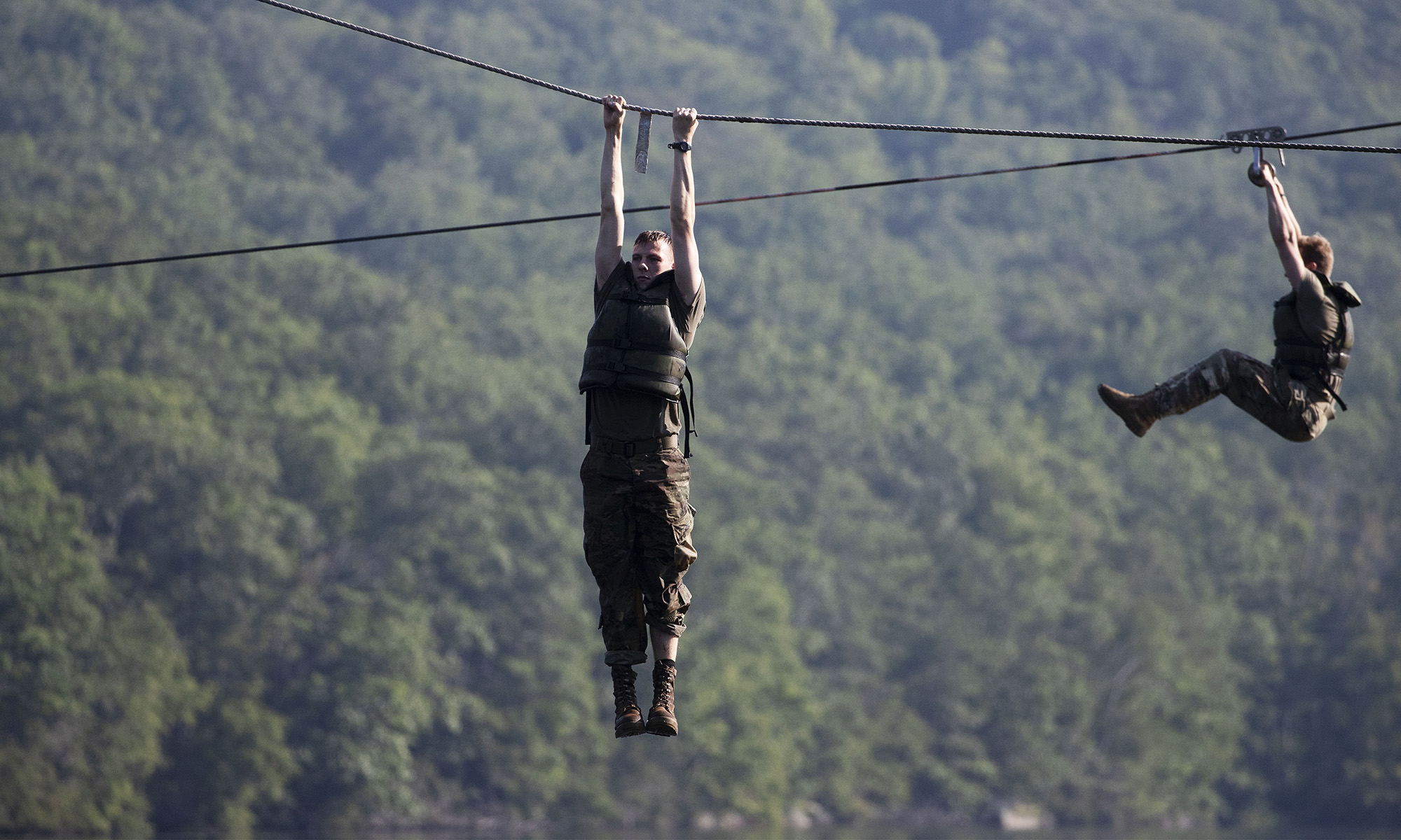 Cadets hang above a lake as they navigate a water obstacle course, Friday, Aug. 7, 2020, in West Point, N.Y. (Mark Lennihan/AP)
