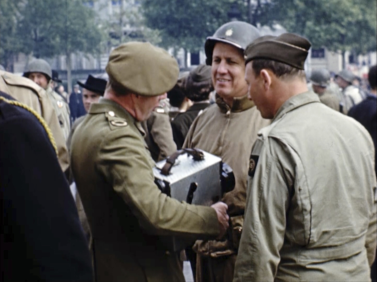 Hollywood director George Stevens, center, talks after a military parade in Paris. Seventy-five years later, surprising color images of the D-Day invasion and aftermath bring an immediacy to wartime memories. They were filmed by Stevens and rediscovered years after his death. (War Footage From the George Stevens Collection at the Library of Congress via AP)