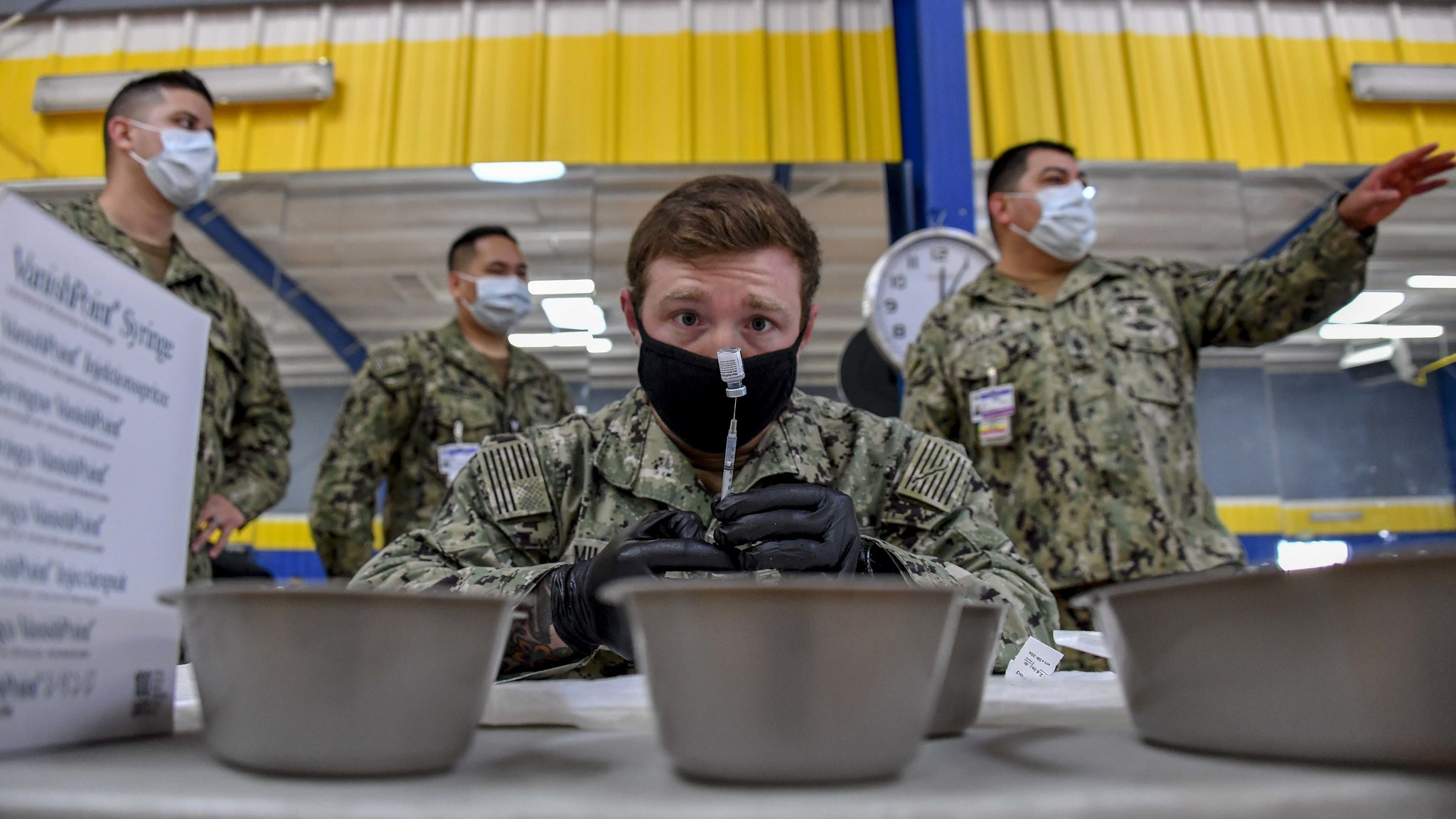 Hospital Corpsman 2nd Class Shane Miller prepares COVID-19 vaccines at the Naval Base San Diego fitness center on Jan. 8, 2020, as part of Operation Warp Speed. (MC1 Julio Rivera/Navy)