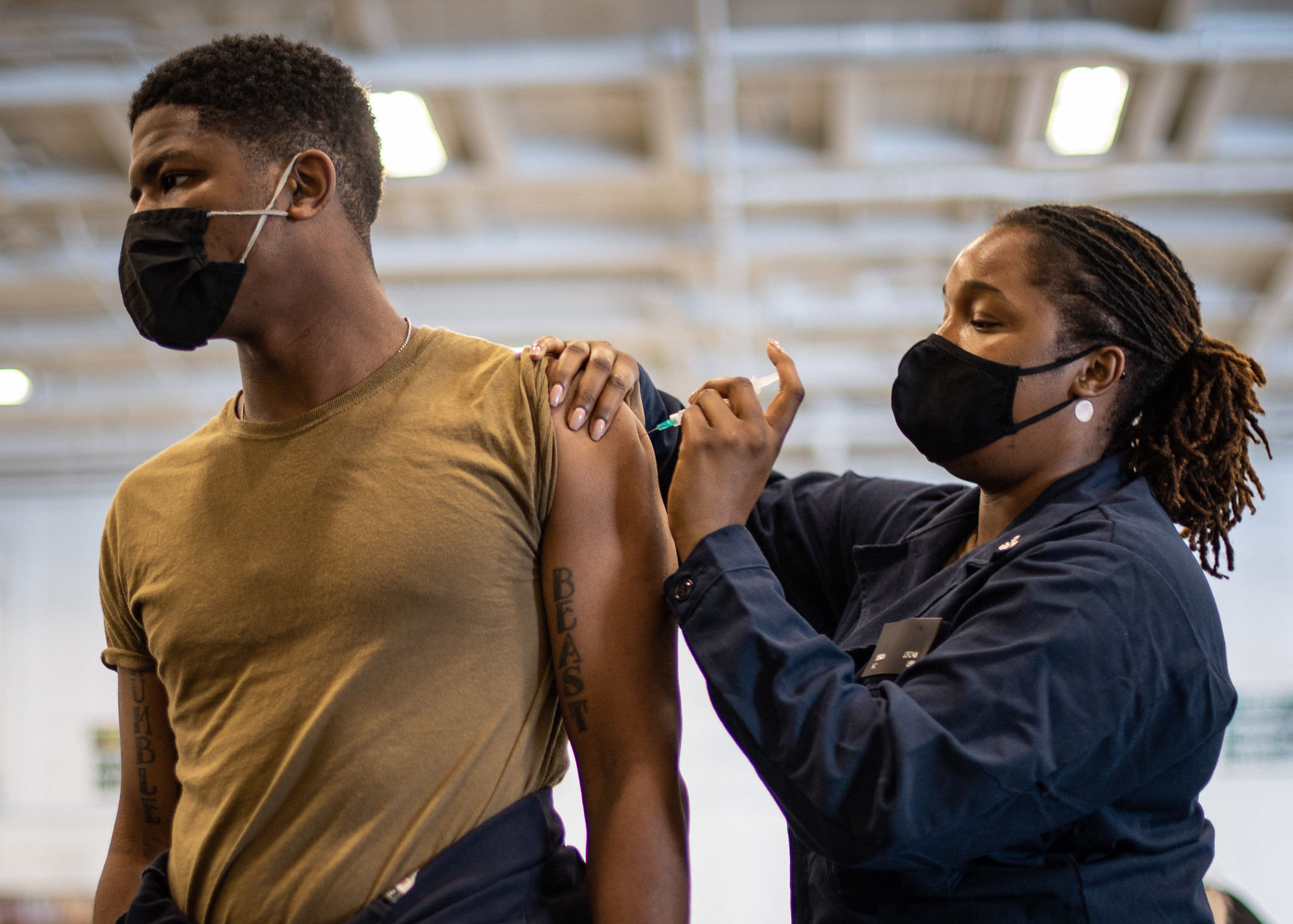 Hospital Corpsman 2nd Class Desirra Jordan administers a flu shot to Aviation Maintenance Administrationman 2nd Class Logan Ray in the hangar bay of the aircraft carrier USS Theodore Roosevelt (CVN 71), Oct. 15, 2020. (MC2 Zachary Wheeler/Navy)