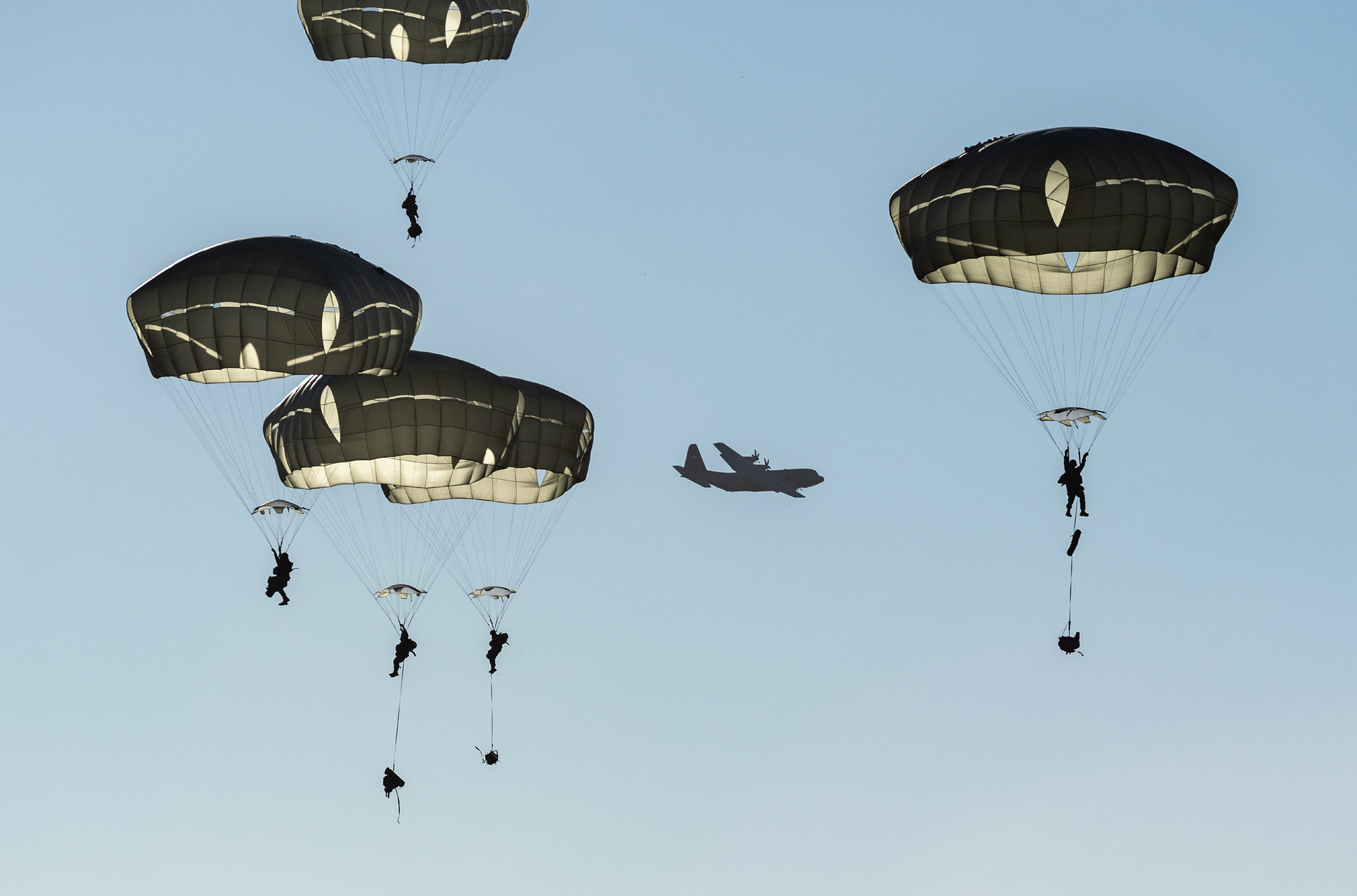 Paratroopers descend over Malemute Drop Zone after jumping from a U.S. Air Force C-130J Super Hercules during airborne training at Joint Base Elmendorf-Richardson, Alaska, Oct. 22, 2020. (Alejandro Pena/Air Force)
