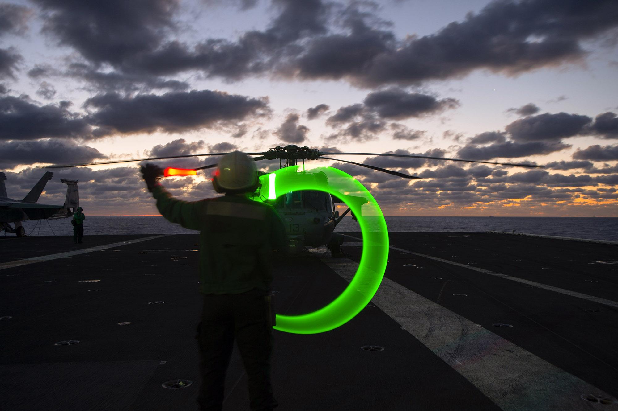 Aviation Structural Mechanic Airman Monica Smith directs a test of an alert helicopter on the flight deck aboard the Nimitz-class aircraft carrier USS Dwight D. Eisenhower (CVN 69), in the Mediterranean Sea, March 19, 2021. (Mass Communication Specialist Seaman Trent P. Hawkins/Navy)