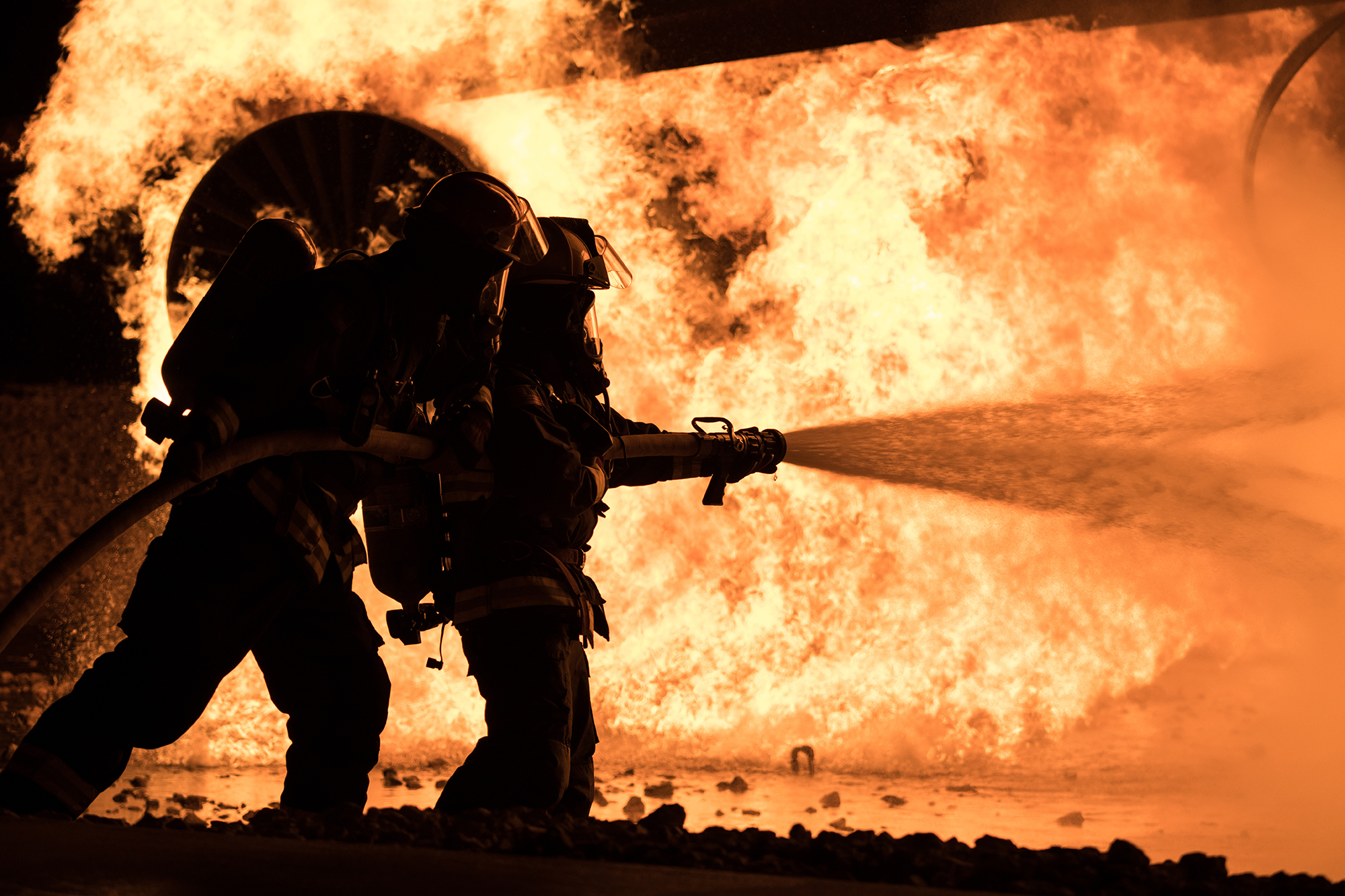 Brent Hardsaw, 22nd Civil Engineer Squadron fire inspector, and Airman 1st Class Trace James, 22nd CES fire protection apprentice, extinguish flames during an annual night aircraft burn, Sept. 18, 2020, at McConnell Air Force Base, Kan. (Senior Airman Alan Ricker/Air Force)