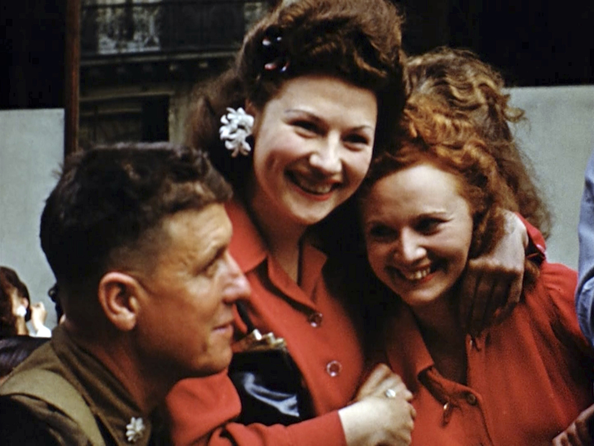 French women smile at U.S. soldiers after the liberation of Paris. Seventy-five years later, surprising color images of the D-Day invasion and aftermath bring an immediacy to wartime memories. They were filmed by Hollywood director George Stevens and rediscovered years after his death. (War Footage From the George Stevens Collection at the Library of Congress via AP)