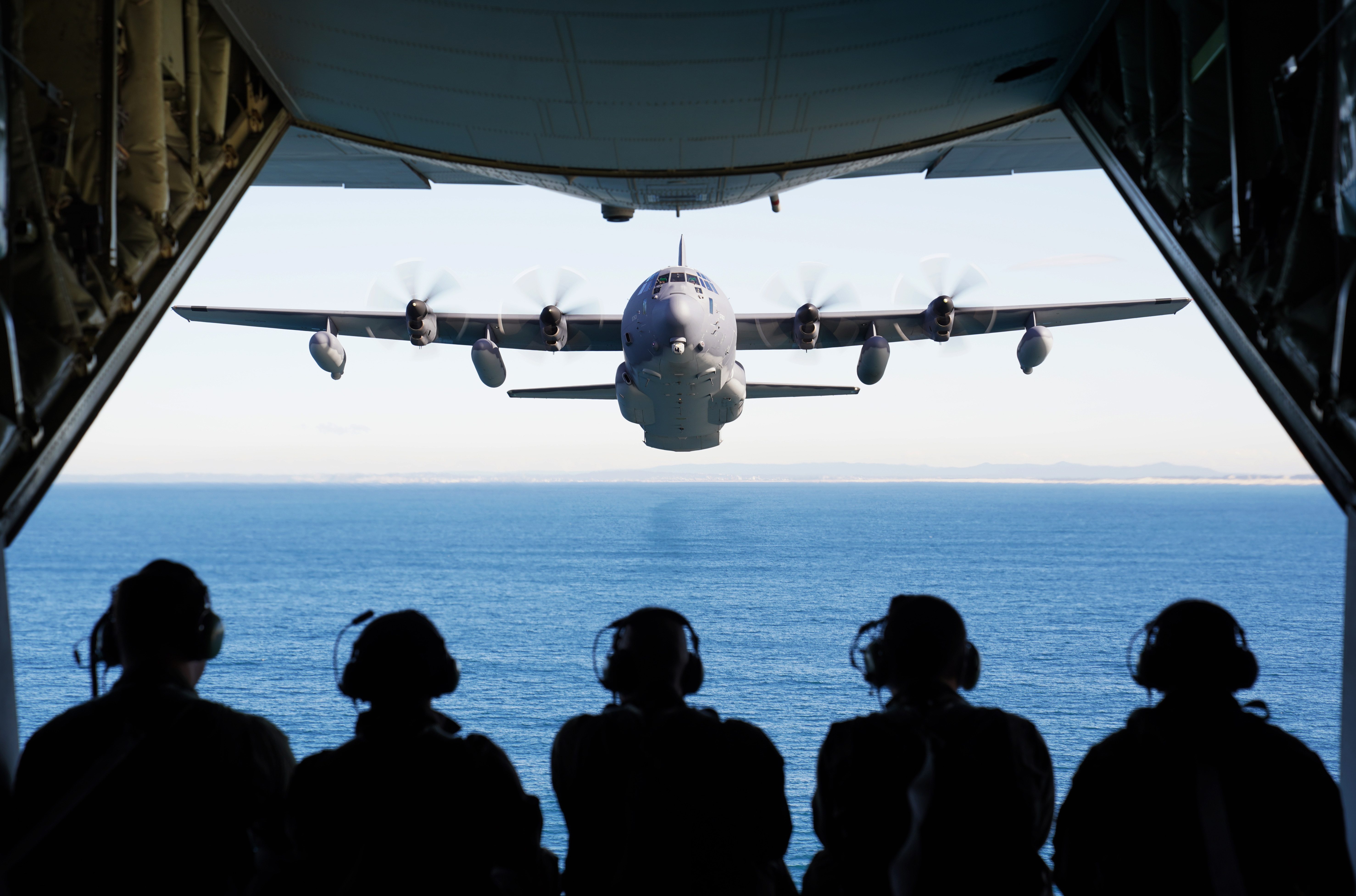 U.S. and Royal Australian Air Force airmen observe an MC-130J Air Commando II flying in formation off the coast of New South Wales, Australia, during exercise Teak Action 21 July 3. (1st Lt. Joshua Thompson/Air Force)