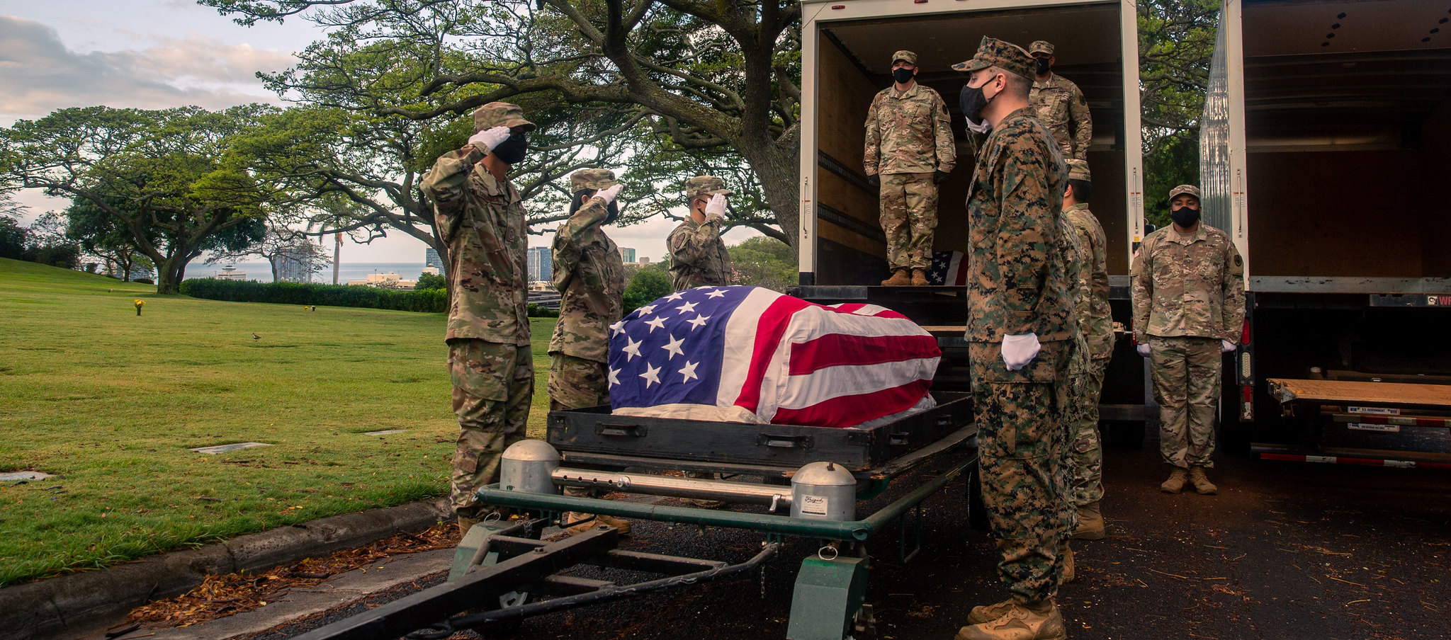 Members of the Defense POW/MIA Accounting Agency (DPAA) salute a casket while participating in a disinterment ceremony at the National Memorial Cemetery of the Pacific, Honolulu, Hawaii, April 19, 2021. The ceremony was part of DPAA's efforts to disinter the remains of unknown service members lost during the Korean War. (Sgt. Jacqueline A. Clifford/Marine Corps)