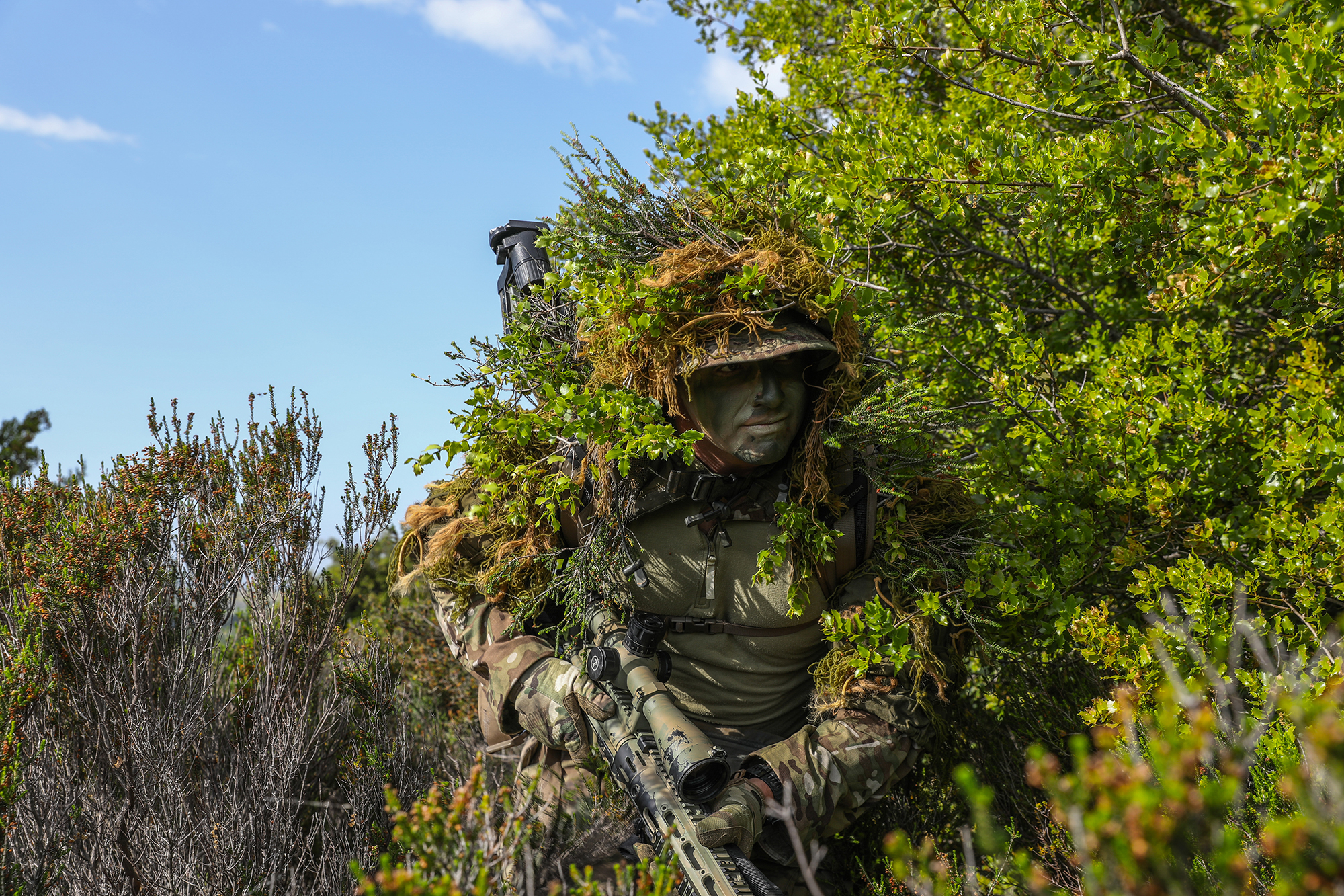 Alabama Army National Guardsman Spc. Dexter Hanson meshes his ghillie suit with the surrounding brush for better concealment during a training exercise in Xanthi, Greece, May 18, 2021. (Sgt. Samuel Hartley/Army)