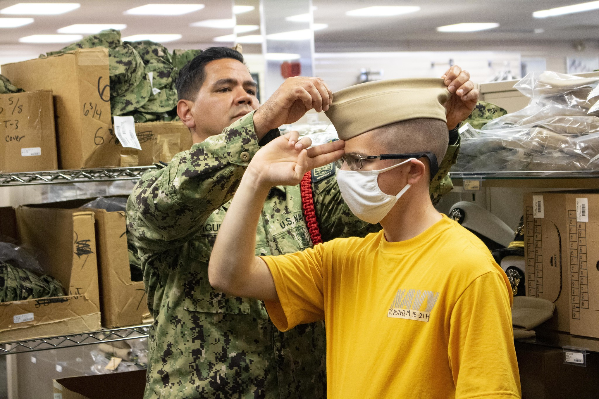 Chief Engineman Alexander Figueroa fits a garrison cover on an Officer Candidate School (OCS) student on June 3, 2021, at Officer Training Command Newport, in Newport, R.I. (Officer Candidate Andrea Perez/Navy)