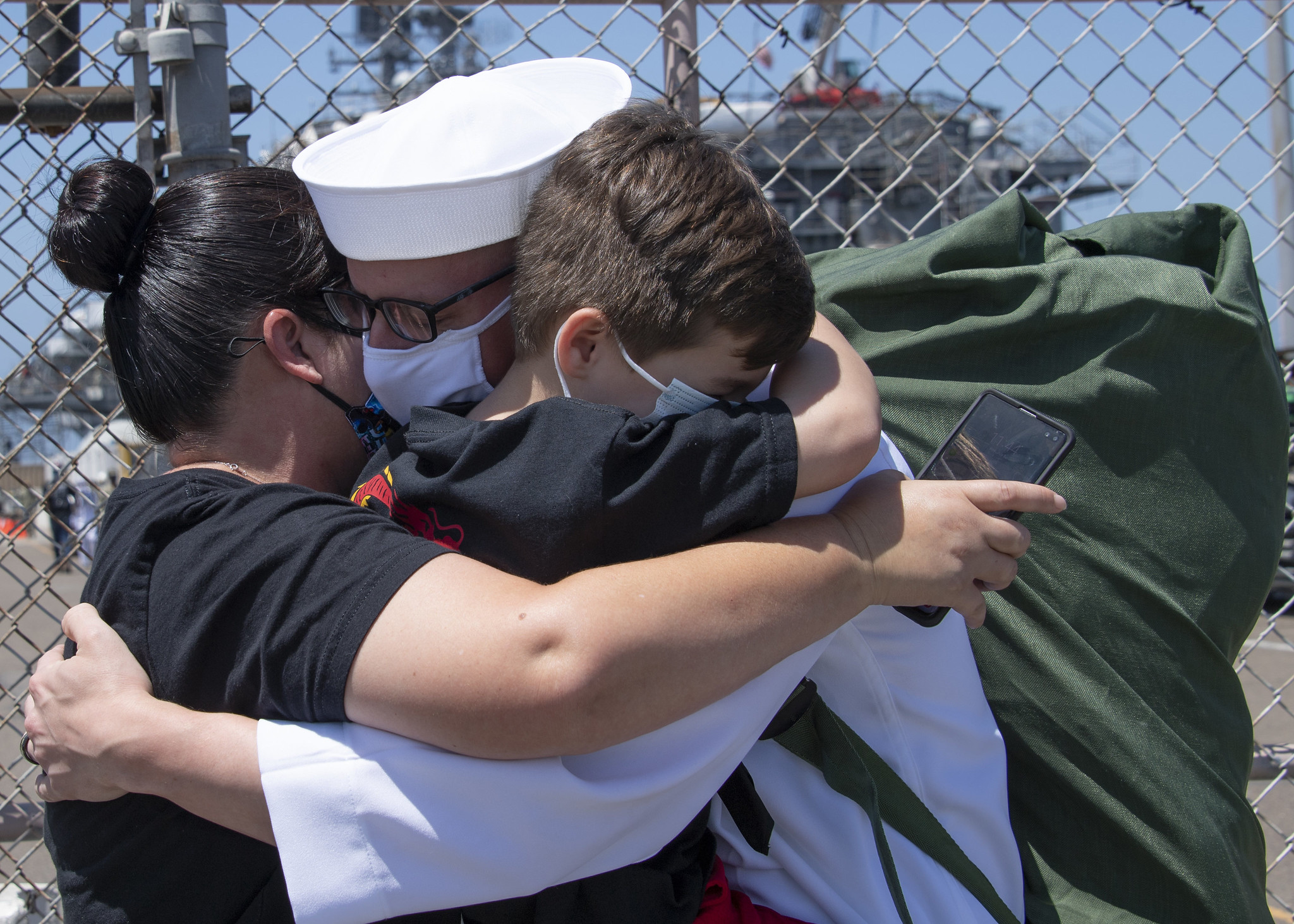 Electronics Technician 1st Class Vincent Testagrossa, assigned to the guided-missile destroyer USS Russell (DDG 59), hugs his family following Russell's return to Naval Base San Diego on July 8, 2020, after a six-month deployment in support of maritime security operations and theater security cooperation efforts in the U.S. 7th Fleet area of operations. (MC3 Kevin C. Leitner/Navy)