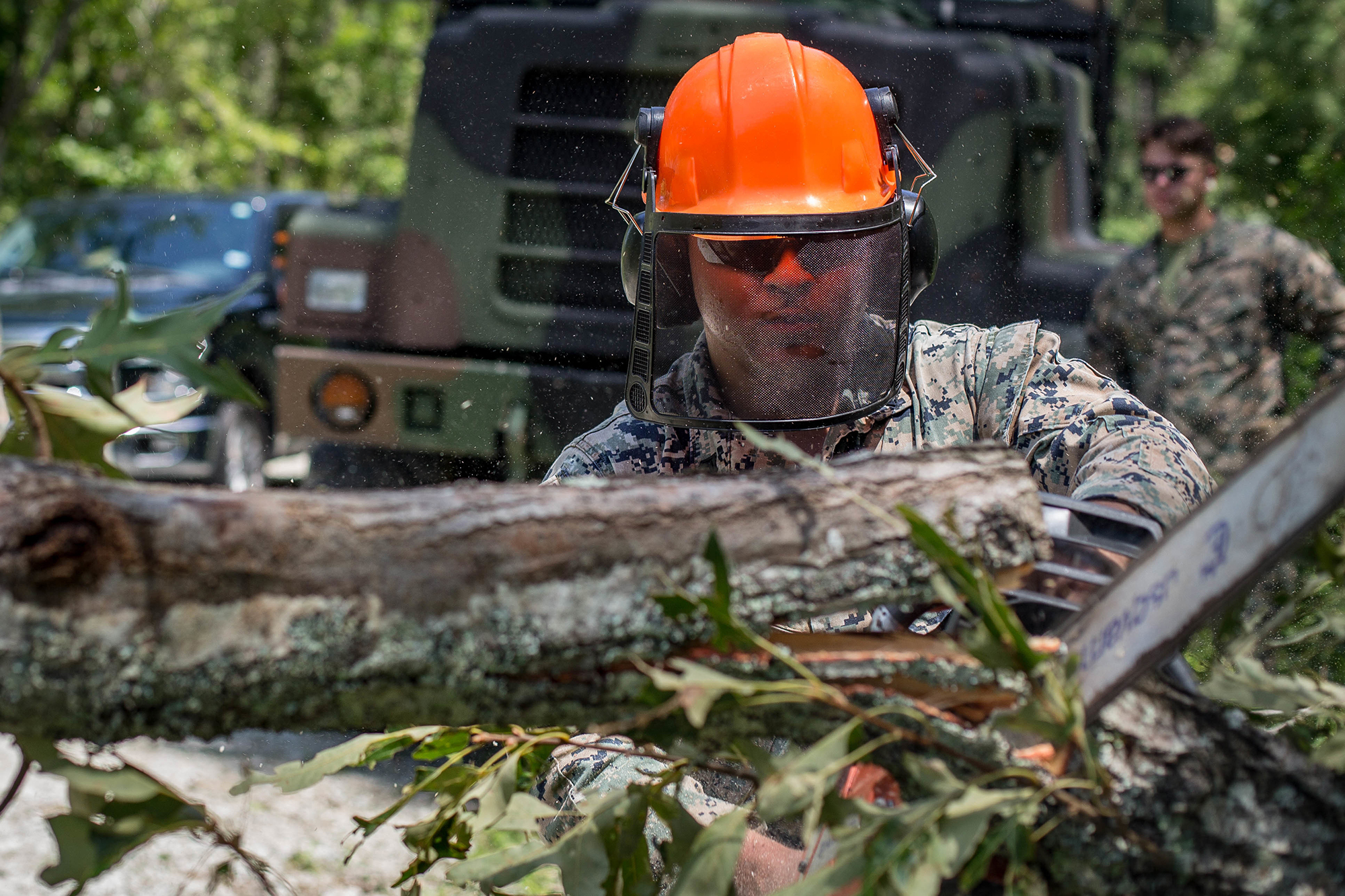 Cpl. William Butler uses a chainsaw to clear debris on a training area road at Marine Corps Air Station New River, N.C., Aug. 4, 2020, after Hurricane Isaias in order to resume normal operations. (Lance Cpl. Scott Jenkins/Marine Corps)
