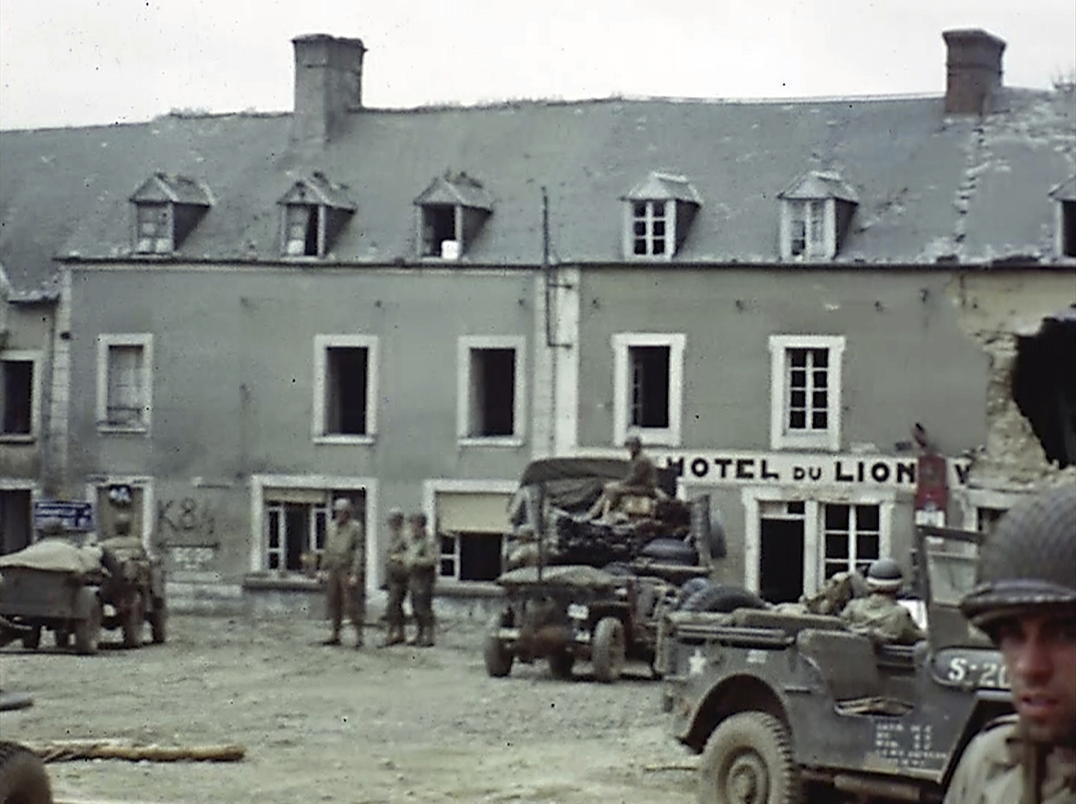 U.S. troops drive through a town by a sign for the Hotel du Lion during World War II in France. Seventy-five years later, surprising color images of the D-Day invasion and aftermath bring an immediacy to wartime memories. They were filmed by Hollywood director George Stevens and rediscovered years after his death. (War Footage From the George Stevens Collection at the Library of Congress via AP)