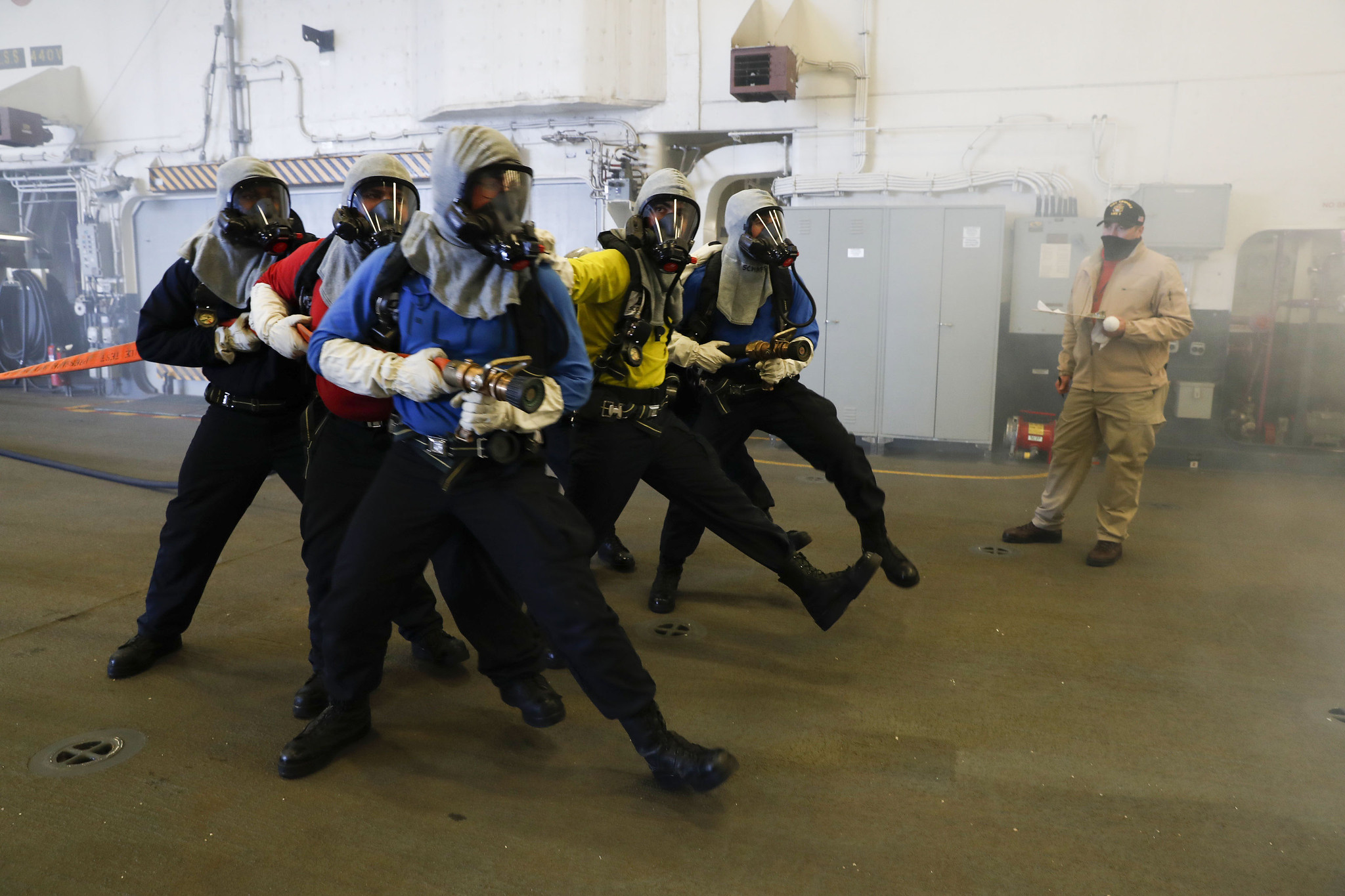 Aviation boatswain's mates (handling) simulate approaching a fire during an aircraft firefighting drill in the hangar bay of the amphibious assault ship USS Tripoli (LHA 7), Aug. 31, 2020, in the Pacific Ocean. (MC1 Christopher B. Janik/Navy)