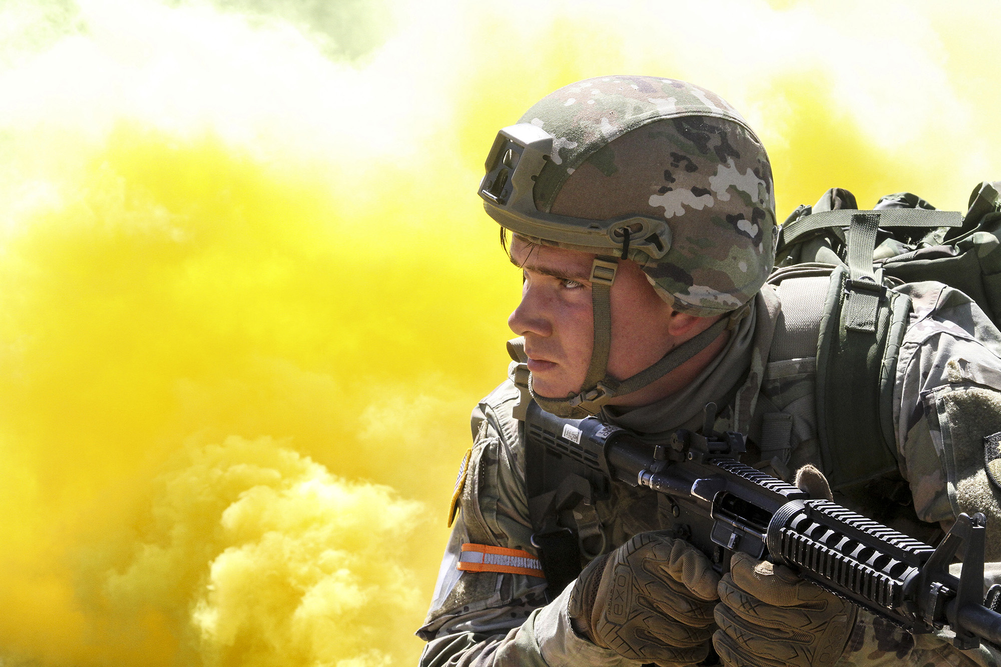Yellow smoke billows as Spc. Caleb Romero of the California National Guard's Headquarters Company, 143rd Military Police Battalion, 49th Military Police Brigade, scans his sector March 31, 2021, during the mystery event of Cal Guard's Best Warrior Competition at Camp Roberts, Calif. (Staff Sgt. Eddie Siguenza/Army National Guard)