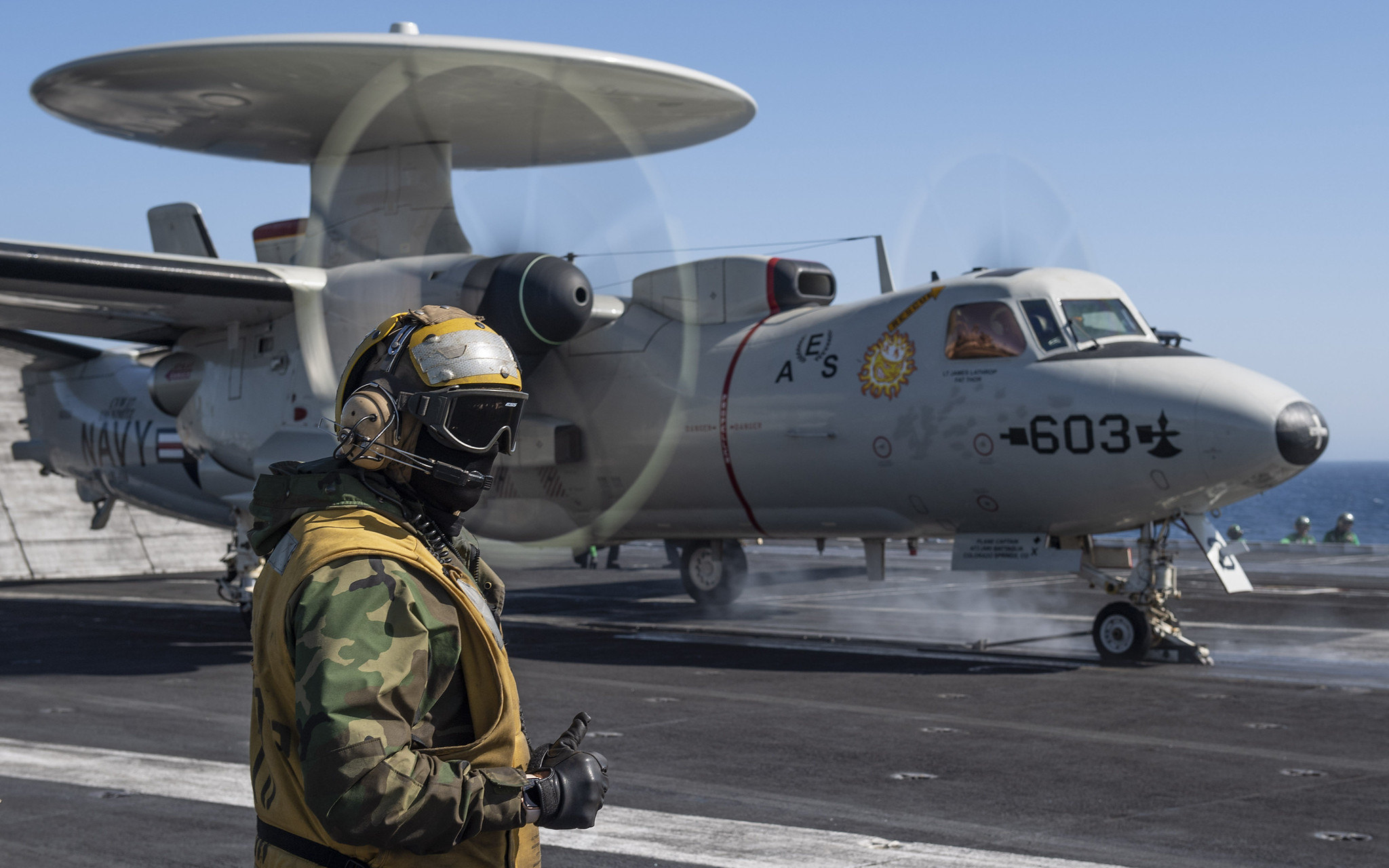 A sailor directs an E-2C Hawkeye on the flight deck aboard the aircraft carrier USS Nimitz (CVN 68) on June 8, 2020, in the Pacific Ocean. (MC3 Elliot Schaudt/Navy)