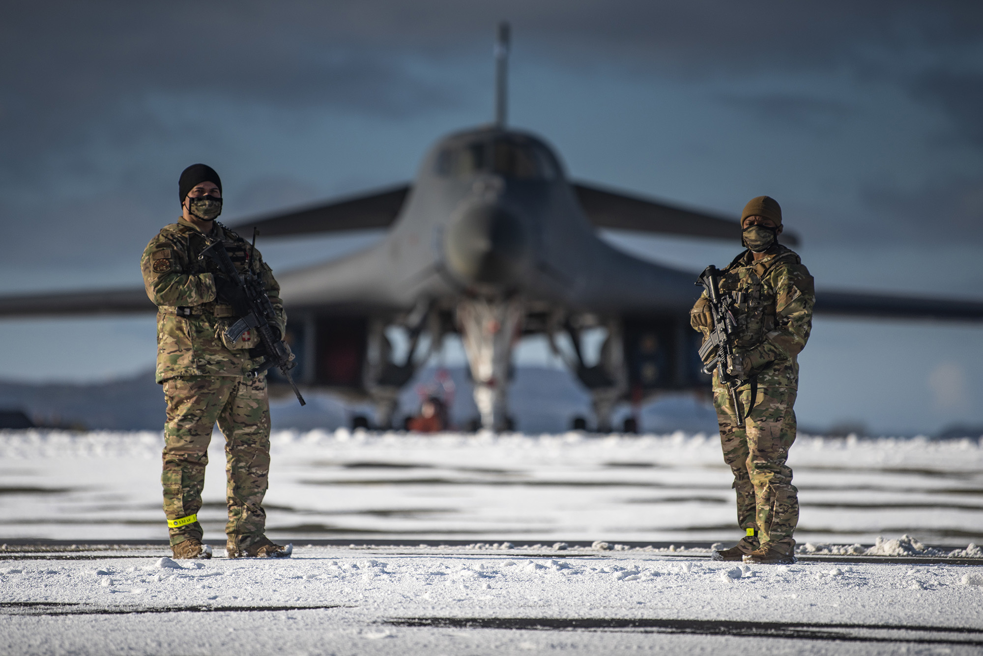 Two defenders assigned to the 7th Security Forces Squadron guard a B-1B Lancer on the flight line at Ørland Air Force Station, Norway, March 7, 2021. (Airman 1st Class Colin Hollowell/Air Force)