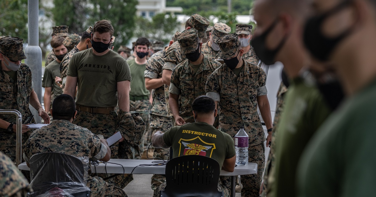 U.S. Marines queue up to receive the Moderna coronavirus vaccine April 28 at Camp Hansen on Okinawa, Japan. The services have urged troops to take the shots, but haven't forced them. (Carl Court/Getty Images)