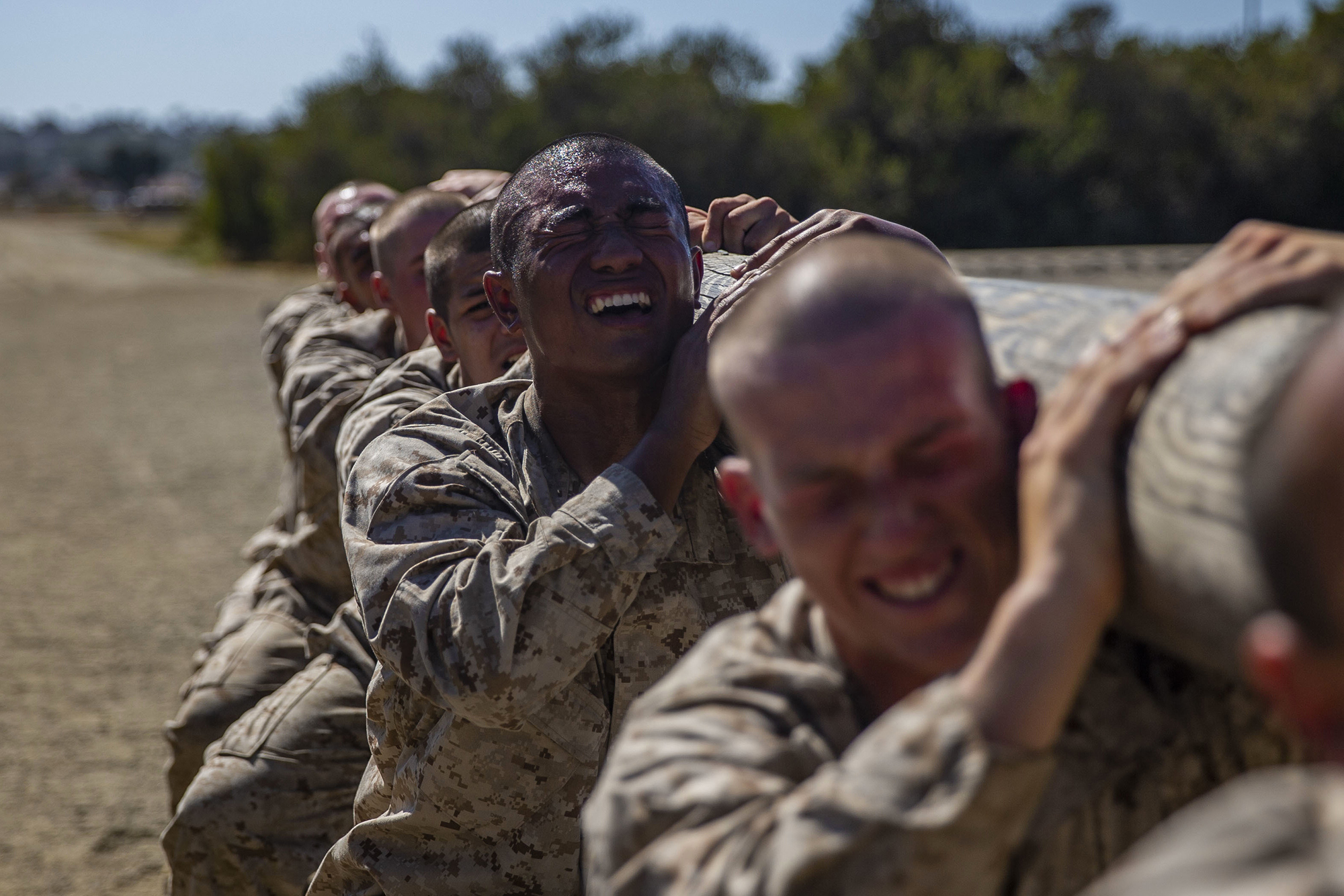 Recruits with Golf Company, 2nd Recruit Training Battalion, execute squats with a log during log drills at Marine Corps Recruit Depot San Diego on May 25, 2021, in California. (Lance Cpl. Grace J. Kindred/Marine Corps)