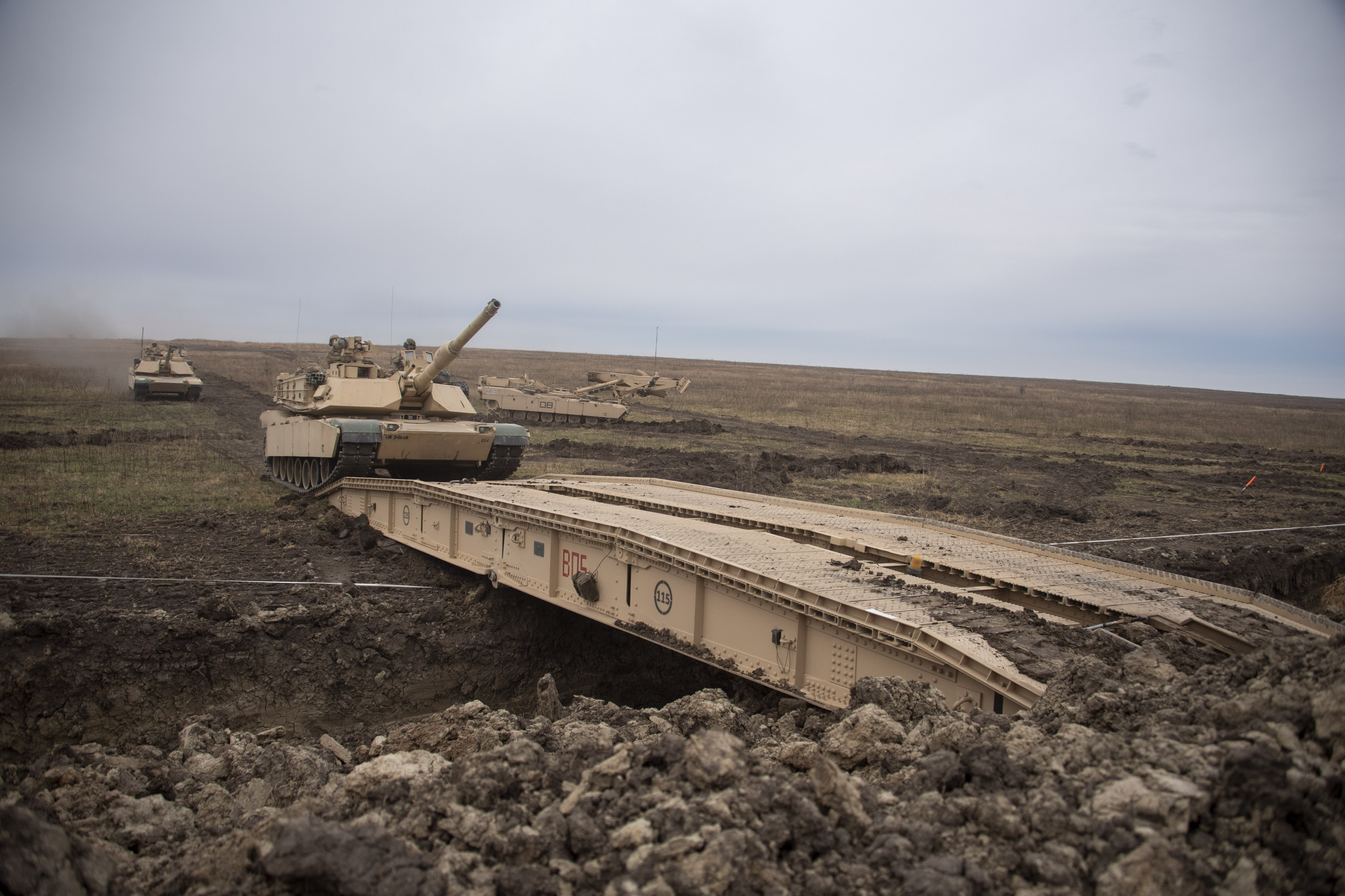 An M1A1 Abrams tank crosses a heavy assault scissor bridge over an anti-vehicle tactical obstacle during operational testing of the Joint Assault Bridge at Fort Riley, Kan. (Tad Browning/U.S. Army)
