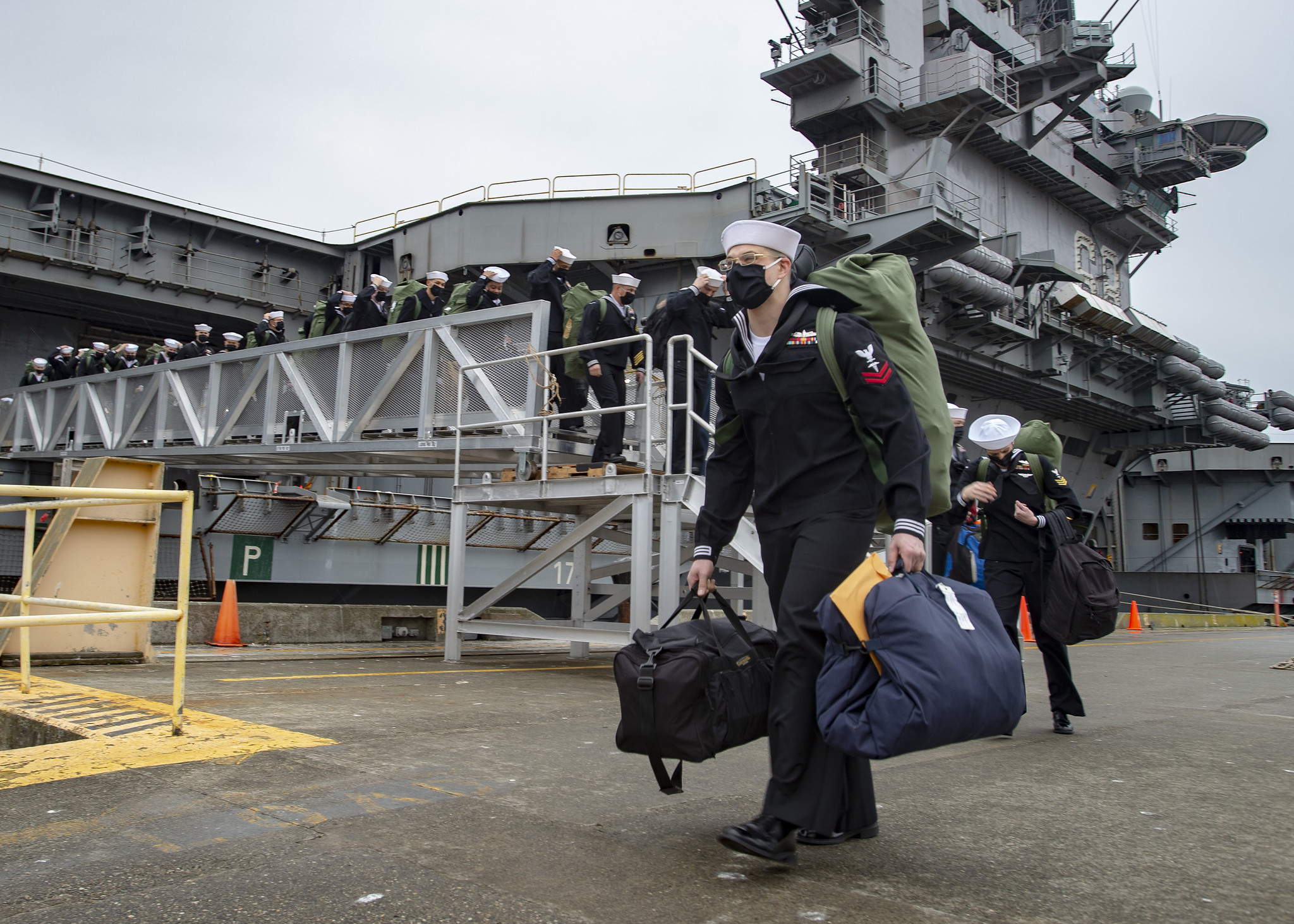 Sailors disembark the aircraft carrier USS Nimitz (CVN 68) at Naval Magazine Indian Island, Wash., on March 4, 2021. Nimitz, part of Nimitz Carrier Strike Group, returned to the Pacific Northwest after more than 11 months following a deployment to U.S. 5th and U.S. 7th Fleets. (MC2 Eleanor Vara/Navy)