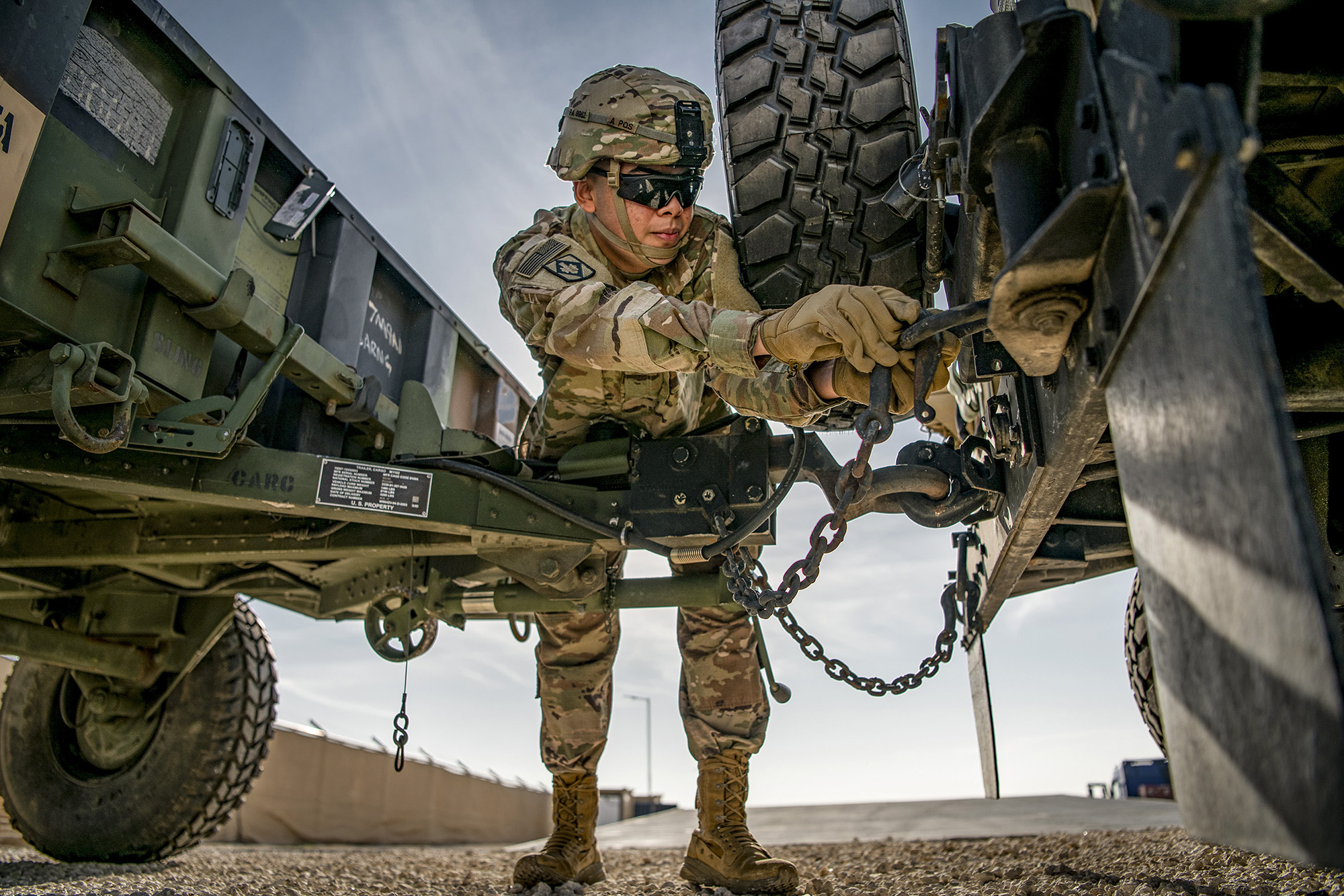 Pvt. 1st Class Pablo Aguirre secures an M1101 trailer to the back of a high mobility multipurpose wheeled vehicle on Dec. 22, 2020, in support of Operation Spartan Shield and Operation Inherent Resolve. (Sgt. Dustin D. Biven/Army)
