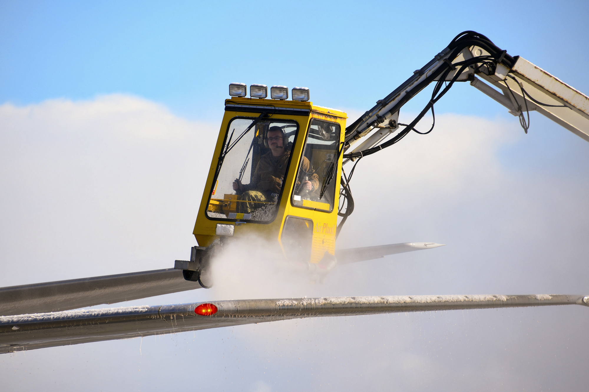 Aviation Machinist's Mate 1st Class Andrew Sutton operates a de-icing truck to remove snow and ice from the wing of a P-8A Poseidon on Nov. 10, 2020, at Misawa Air Base. (Mass Communication Specialist Seaman Benjamin Ringers/Navy)