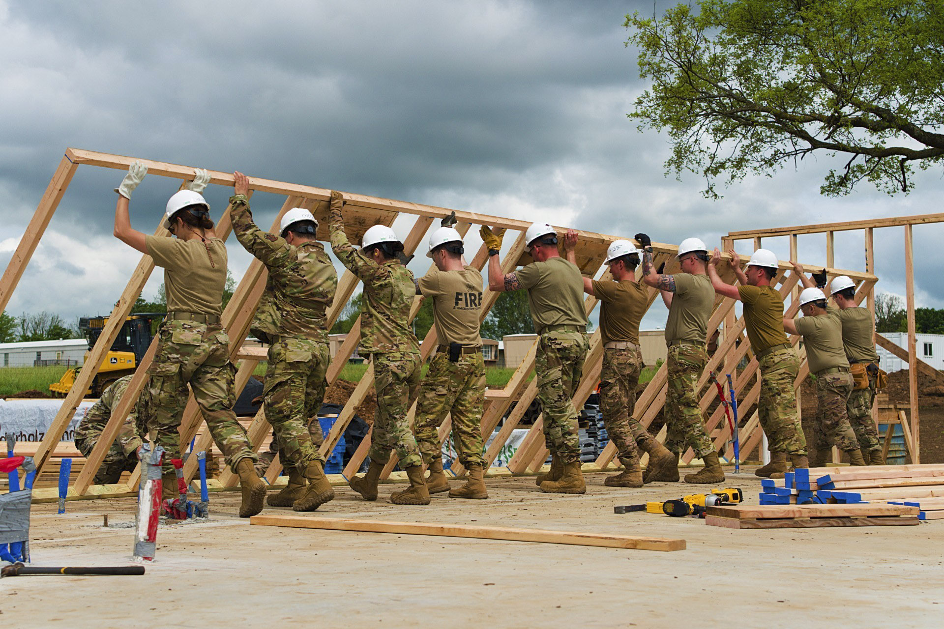 Airmen from all trades, with the 176th Wing's Civil Engineer Squadron, raise the second exterior wall in unison as they construct the first home in the Cherokee Veterans Housing Initiative in Tahlequah, Okla., May 18, 2021. The initiative is a collaboration between the Department of Defense's Innovative Readiness Training program and the Cherokee Nation that constructs new single-family homes and supporting infrastructure for eligible Cherokee Nation veterans and their families. (Staff Sgt. Clay Cook/Air National Guard)