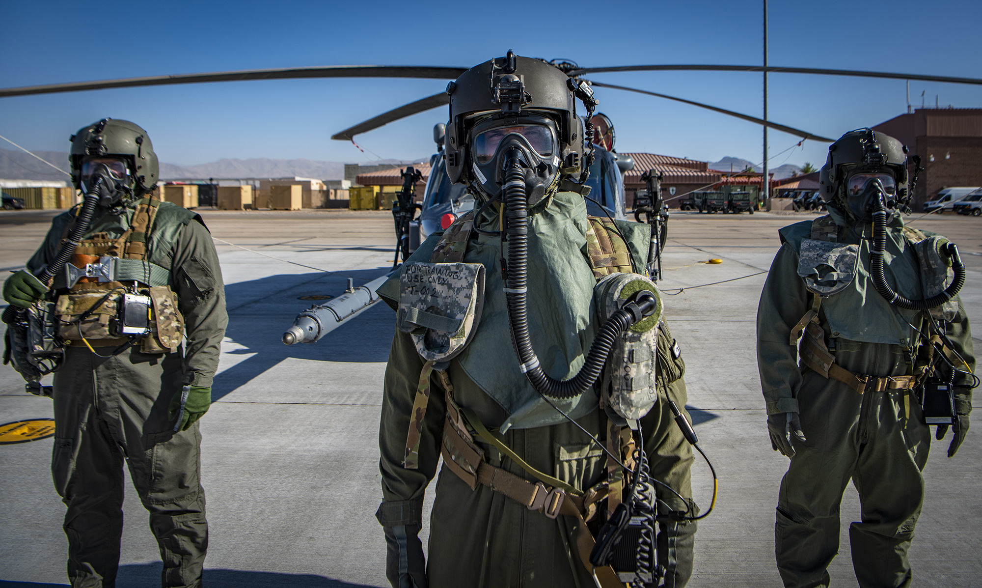 Airmen assigned to the 88th Test and Evaluation Squadron pose for a photo in full Chemical, Biological, Radiological, and Nuclear flight gear during a developmental test at Nellis Air Force Base, Nev., April 21, 2021. The airmen participated in on-going testing of the new Uniform Integrated Protective Ensemble Air two-piece system. (Senior Airman Dwane R. Young/Air Force)