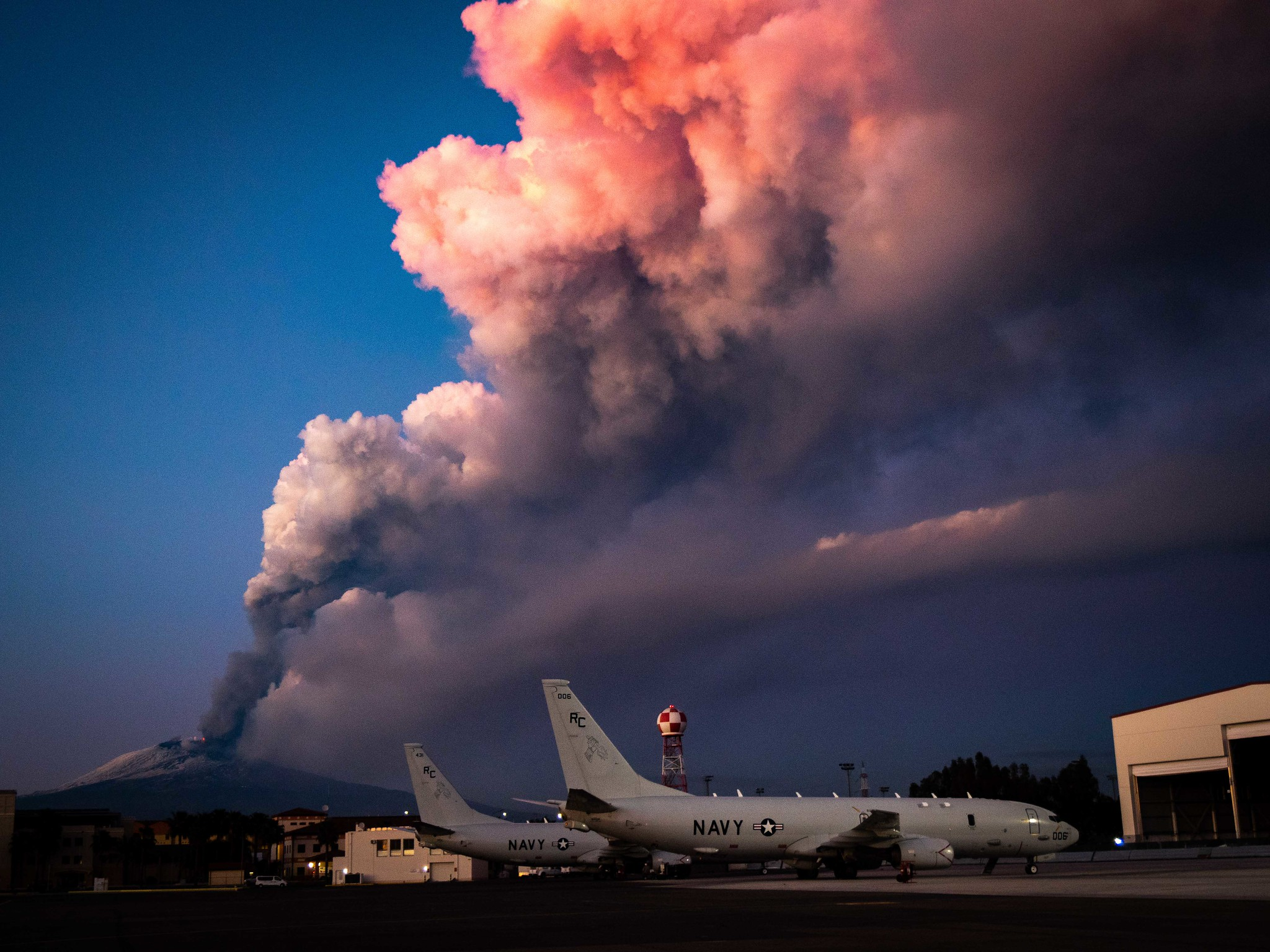 Mount Etna lets off some steam in the background of P-8A Poseidon maritime patrol aircraft Feb. 16, 2021, at Sigonella, Italy. (MC2 Austin Ingram/Navy)