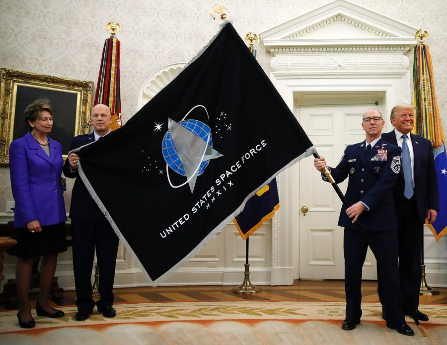 Chief Master Sgt. Roger Trowberman, second from right, unfurls the Space Force flag in a White House ceremony on May 15, 2020, with Chief of Space Operations Gen. Jay Raymond flanked by President Donald Trump, right, and Air Force Secretary Barbara Barrett. (Alex Brandon/AP)