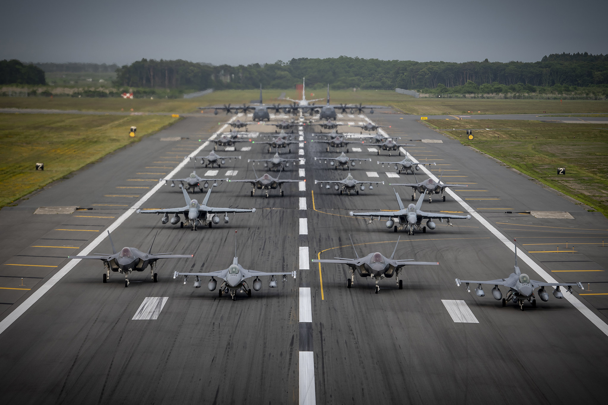 """Twelve U.S. Air Force F-16CM Fighting Falcons, 12 Koku-Jieitai F-35A Lightning II Joint Strike Fighters, two U.S. Navy EA-18G Growlers, a USN C-12 Huron, two USAF MC-130J Commando II aircraft, and a USN P-8 Poseidon participate in an """"Elephant Walk"""" at Misawa Air Base, Japan, June 22, 2020. It was Misawa Air Base's first time hosting a bilateral and joint Elephant Walk. (Airman 1st Class China M. Shock/Air Force)"""