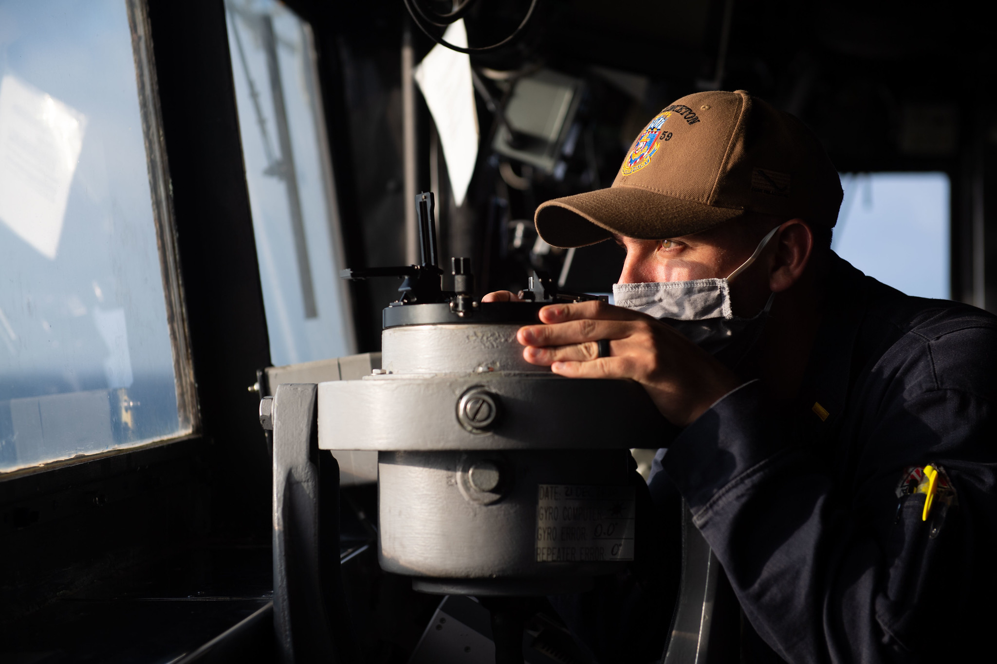 Ensign Chris Luna takes a navigational bearing while standing watch in the pilot house of the guided-missile cruiser USS Princeton (CG 59) on Dec. 21, 2020, in the Indian Ocean. (MC2 Logan C. Kellums/Navy)