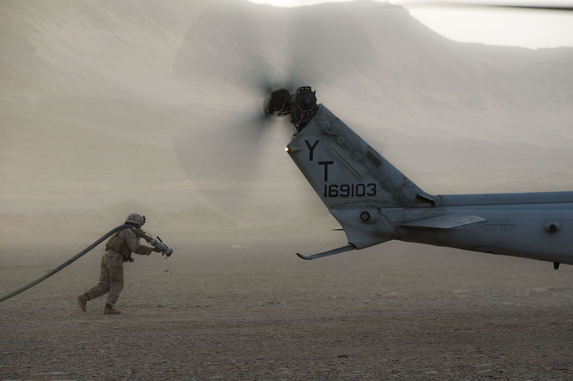 Marine Corps Cpl. Selina Lopez carries a fuel hose to a UH-1Y Venom at a forward arming and refueling point during a theater amphibious combat rehearsal (TACR) in Tabuk, Kingdom of Saudi Arabia, March 9, 2021. (Lance Cpl. Brendan Mullin/Marine Corps)