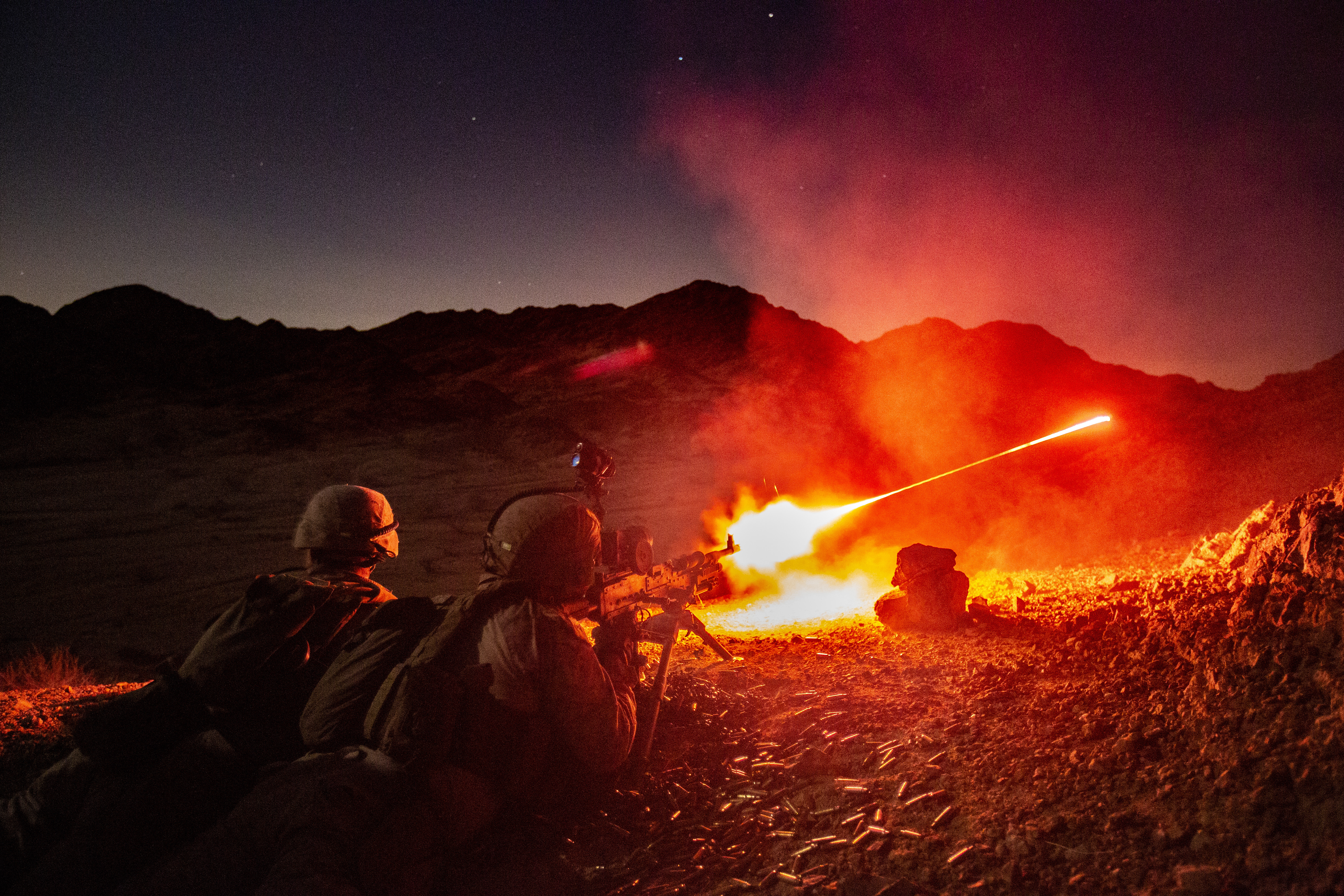 Members of the 24th Marine Expeditionary Unit provide combat support with an M240B medium machine gun while conducting night live-fire platoon assault training at Camp Titin, Jordan, June 21. (1st Lt. Mark Andries/Marine Corps)