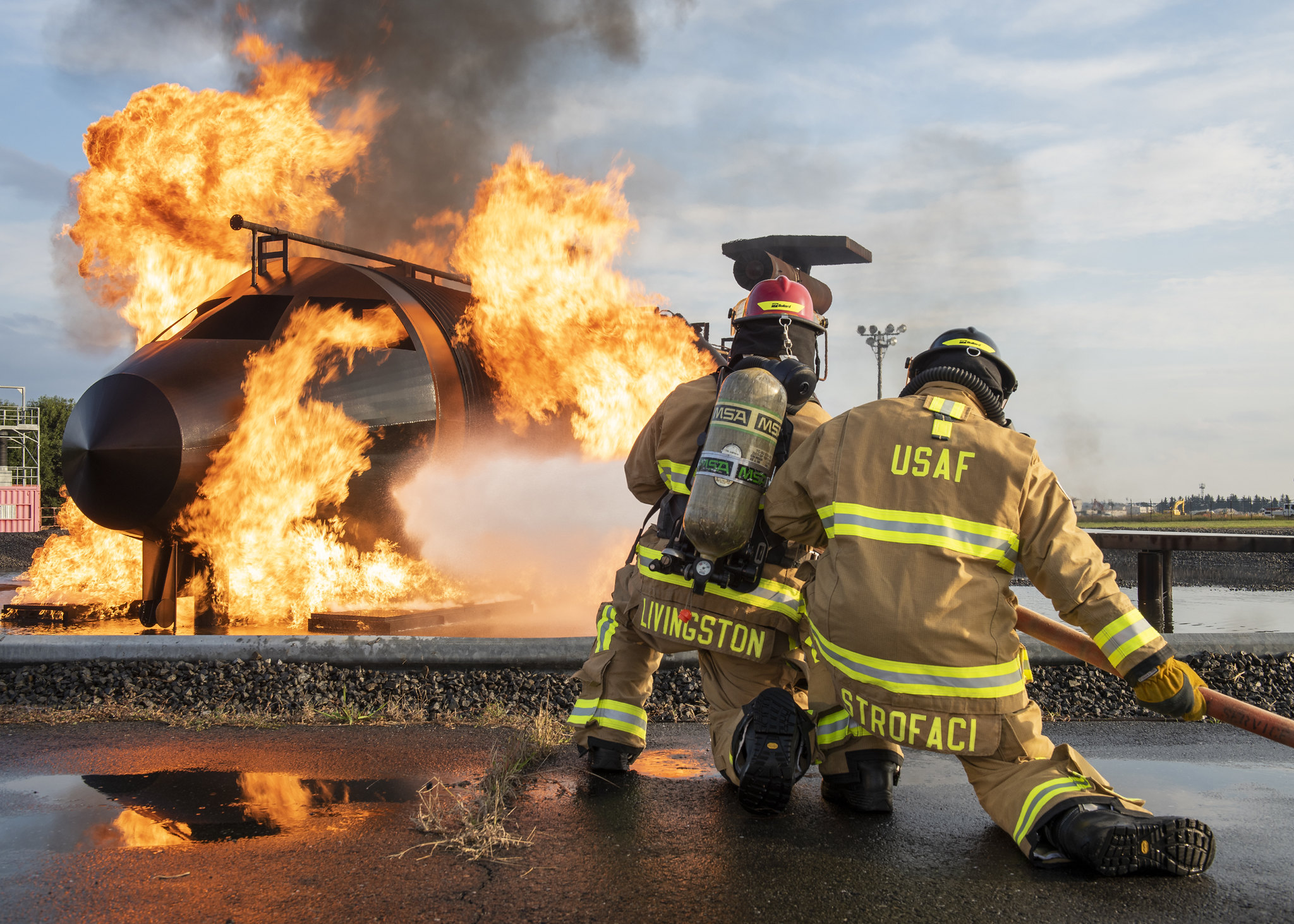Staff Sgt. Dillon Livingston, left, and Senior Airman Jade Strofaci, 374th Civil Engineer Squadron firefighters, participate in a live-fire training scenario, Oct. 27, 2020, at Yokota Air Base, Japan. (Staff Sgt. Juan Torres/Air Force)